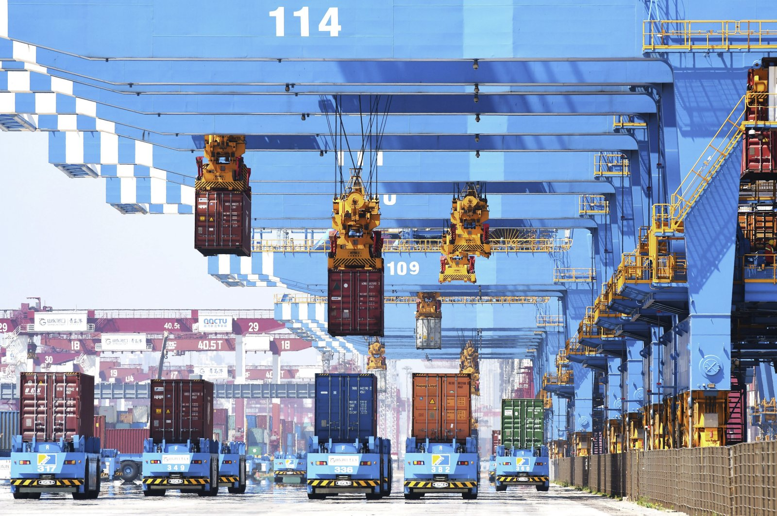 Gantry cranes move containers onto transporters at a port in Qingdao in eastern China's Shandong province, June 4, 2021. (AP Photo)