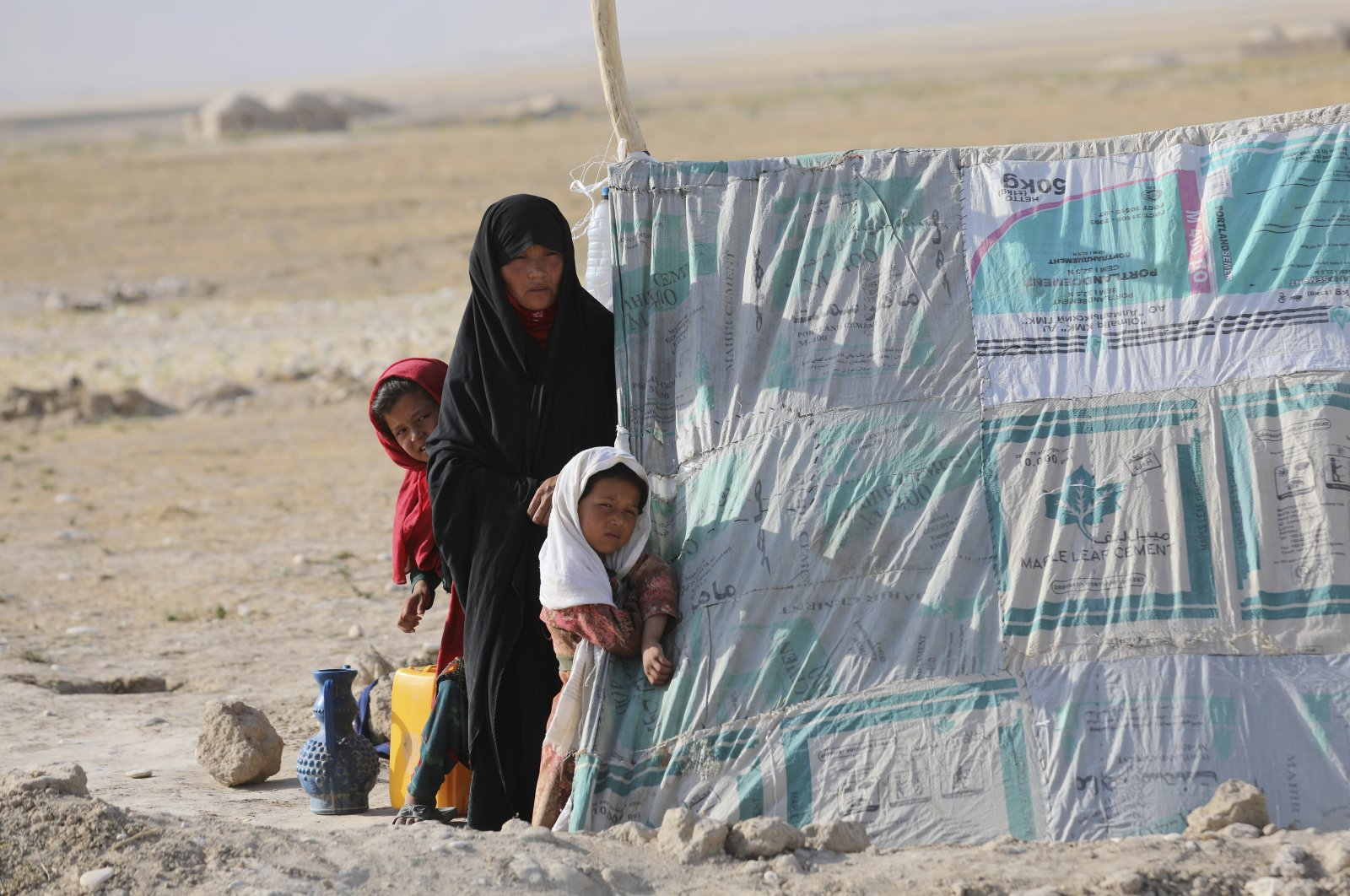 An internally displaced Afghan woman stands with her daughters in front a makeshift tent in a camp on a rocky patch of land, after fleeing fighting between the Taliban and Afghan security personnel, on the edge of the city of Mazar-e-Sharif, northern Afghanistan, July 8, 2021. (AP Photo)