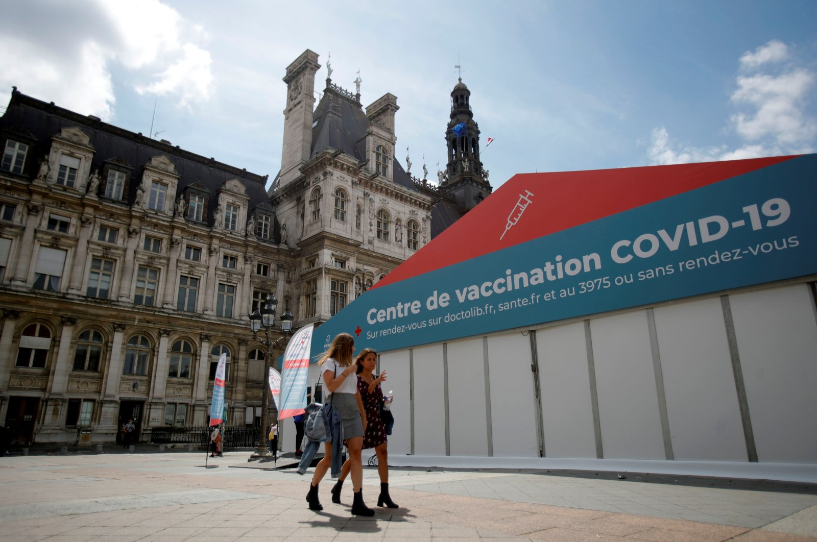 Women walk past a coronavirus vaccination center installed in front of a town hall, Paris, France, July 7, 2021. (Reuters Photo)