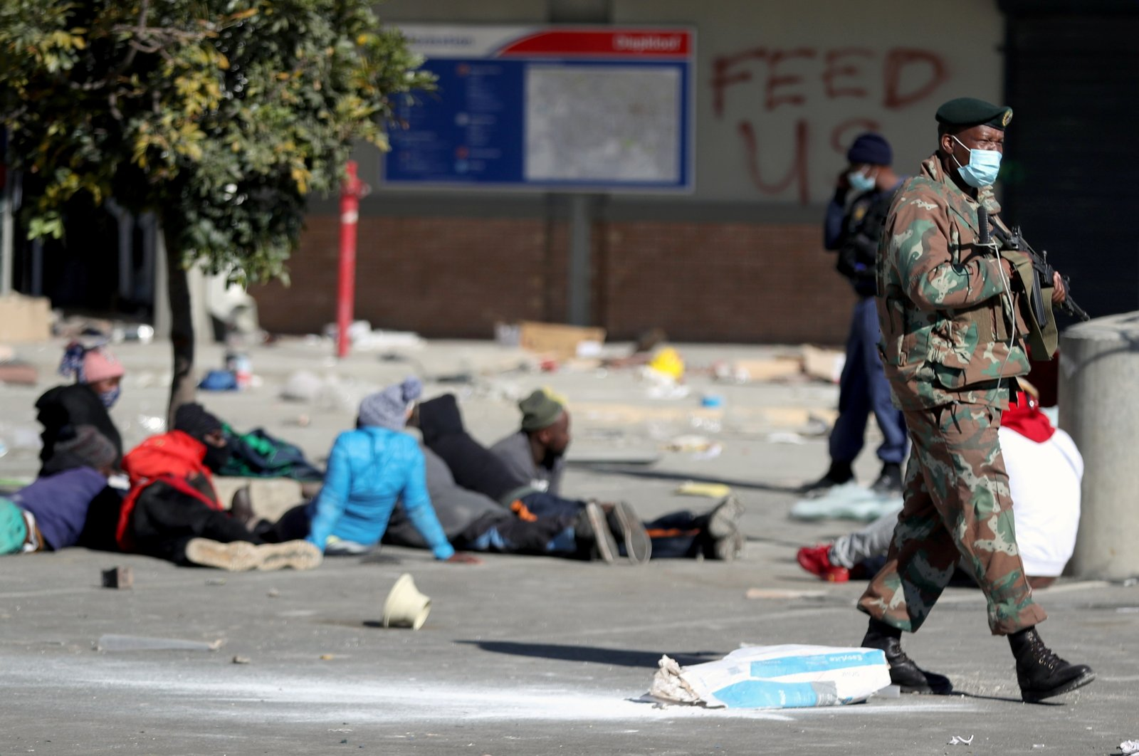 A member of the military keeps guard next to suspected looters outside Diepkloof mall as the country deploys army to quell unrest linked to jailing of former President Jacob Zuma, in Soweto, South Africa, July 13, 2021. (Reuters Photo)