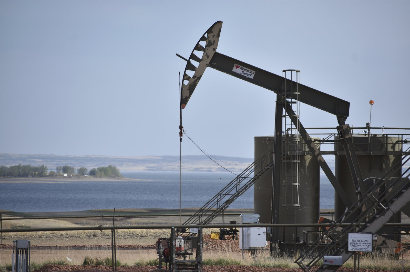 A pump jack extracts oil from beneath the ground on the Fort Berthold Indian Reservation, with Lake Sakakawea in the background, east of New Town, North Dakota, U.S., May 19, 2021. (AP Photo)