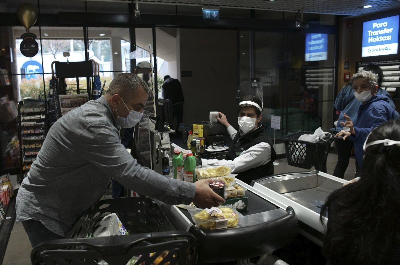 People wearing face masks shop for food at a market in Ankara, Turkey, April 21, 2020. (AP Photo)