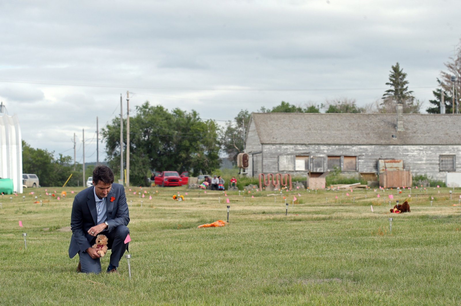 Canada's Prime Minister Justin Trudeau places a teddy bear at an unmarked grave on Cowessess First Nation, where a search found 751 unmarked graves from the former Marieval Indian Residential School near Grayson, Saskatchewan, Canada, July 6, 2021. (Reuters Photo)