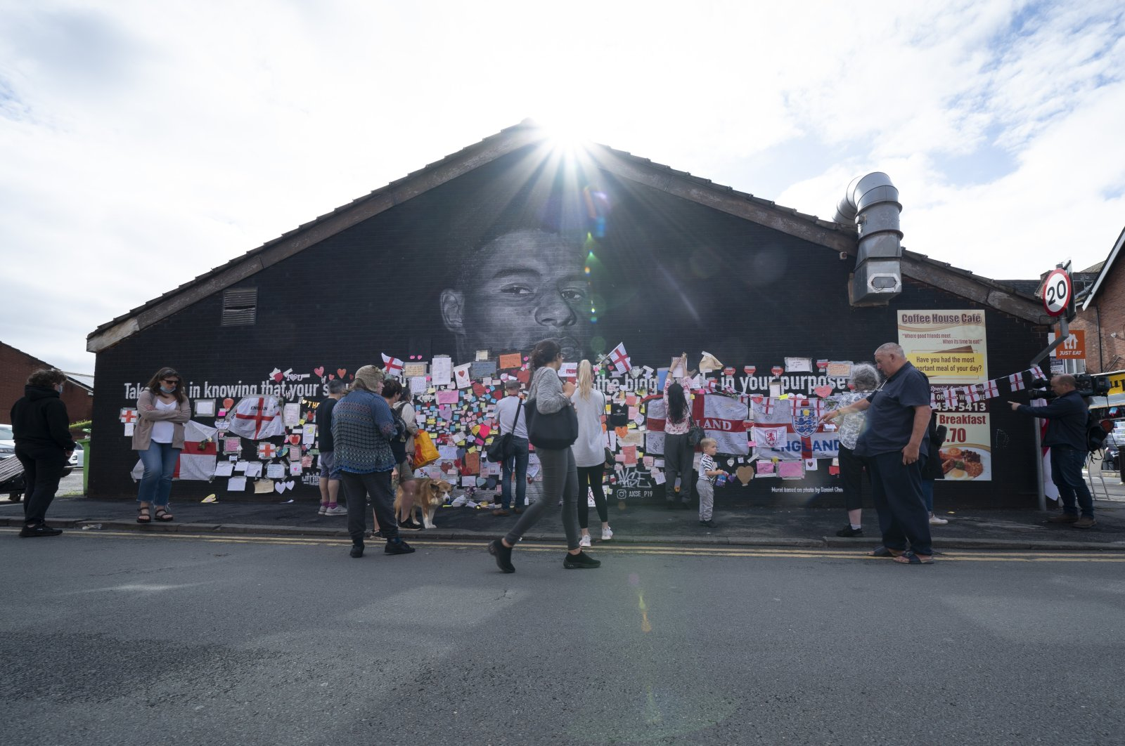 People look at the messages of support left on a mural of Manchester United striker and England player Marcus Rashford, on the wall of the Coffee House Cafe on Copson Street, in Withington, Manchester, England, July 13, 2021. (AP Photo)