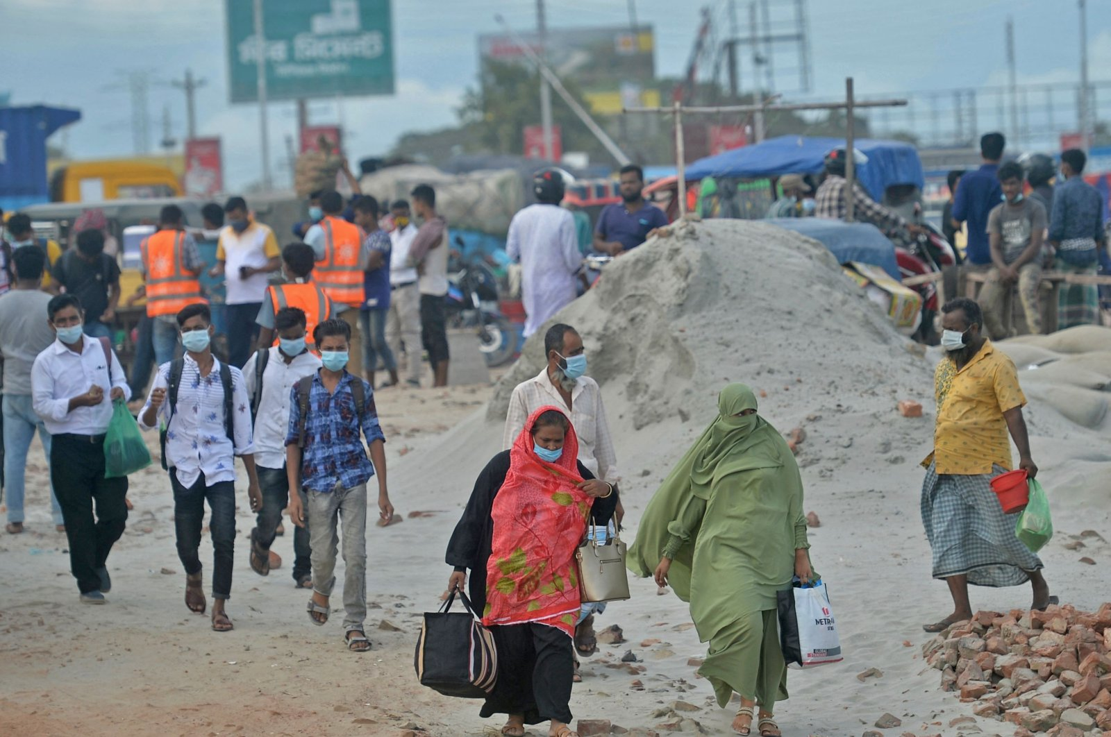 People walk to board a ferry to their hometowns after the government eased a lockdown imposed as a preventive measure against the COVID-19 coronavirus ahead of the Muslim festival of Eid al-Adha in Sreenagar, Bangladesh, July 13, 2021. (AFP Photo)