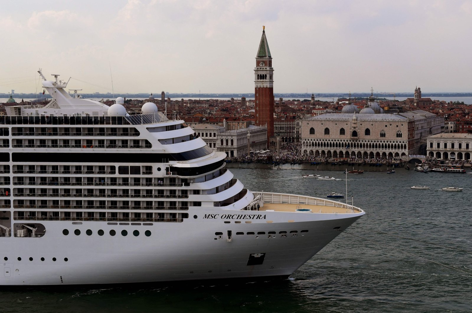 Tugboats escort the MSC Orchestra cruise ship across the basin past the Bell Tower and the Doge's palace as it leaves Venice, Italy, June 5, 2021. (AFP Photo)