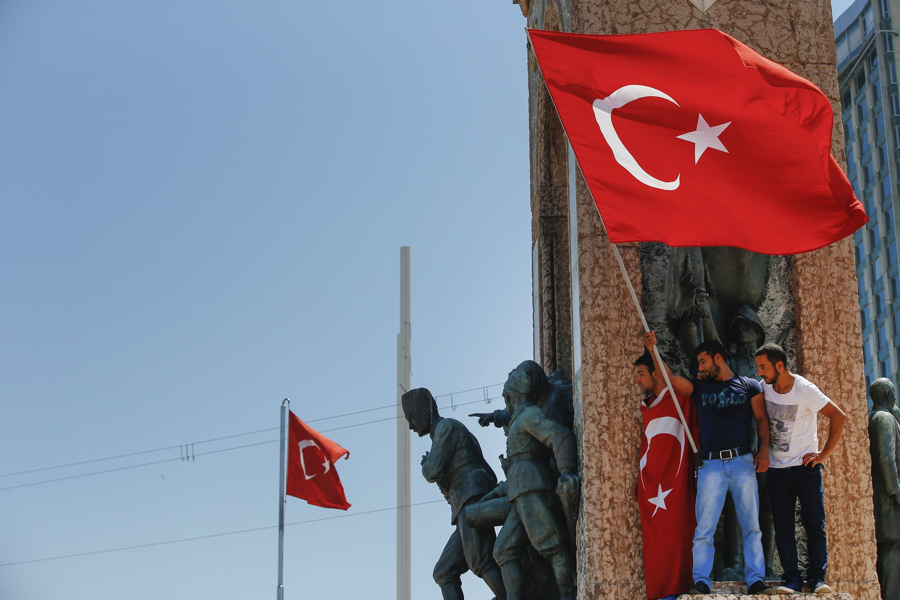People protesting the coup wave a Turkish flag on top of the monument in Taksim Square, Istanbul, Turkey, July 16, 2016. (AP Photo)