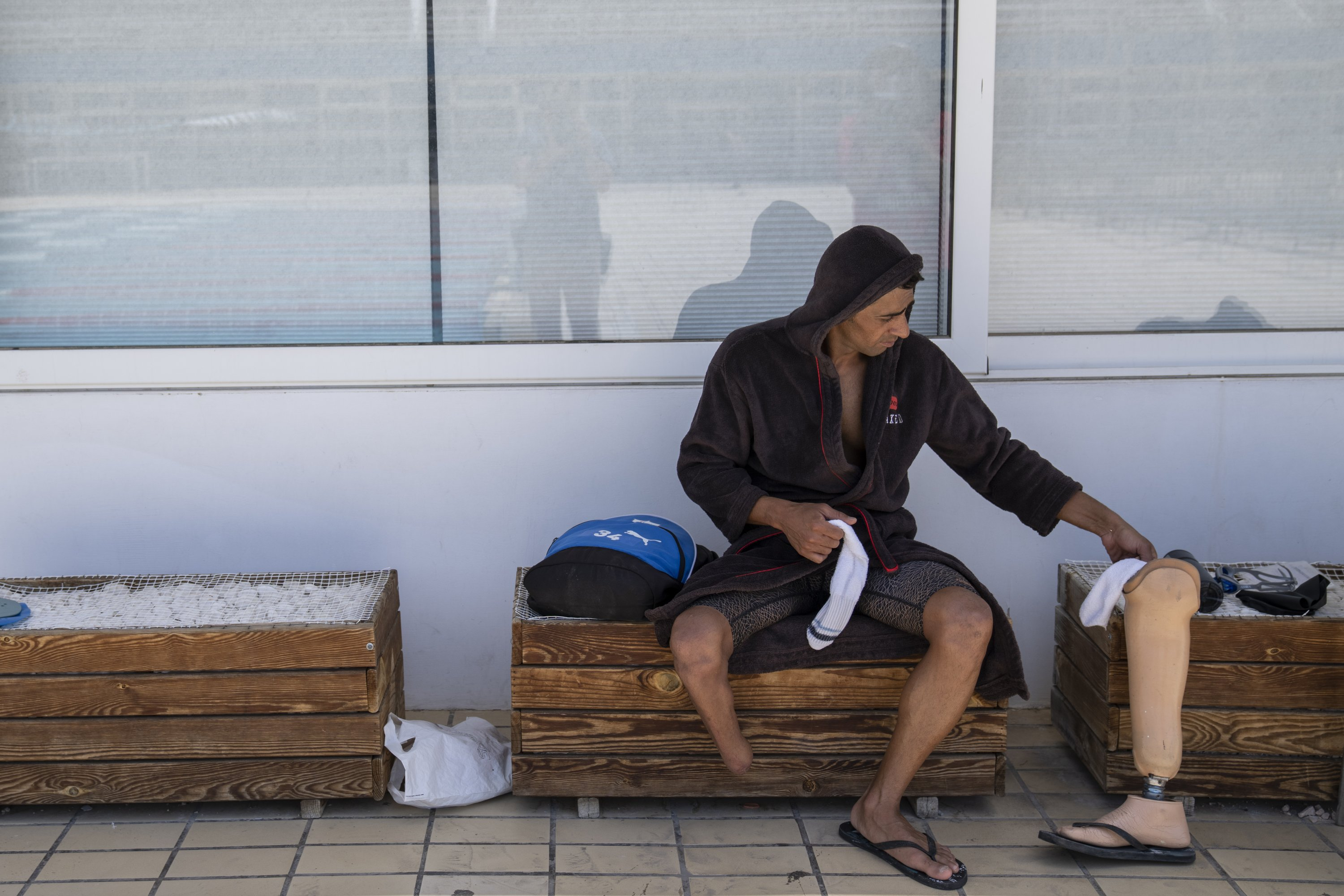 Syrian refugee Ibrahim al-Hussein, an amputee swimmer who lost his leg during the war in Syria, after finishing training at the Olympic Aquatic Center, Athens, Greece, June 30, 2021. (AP Photo)