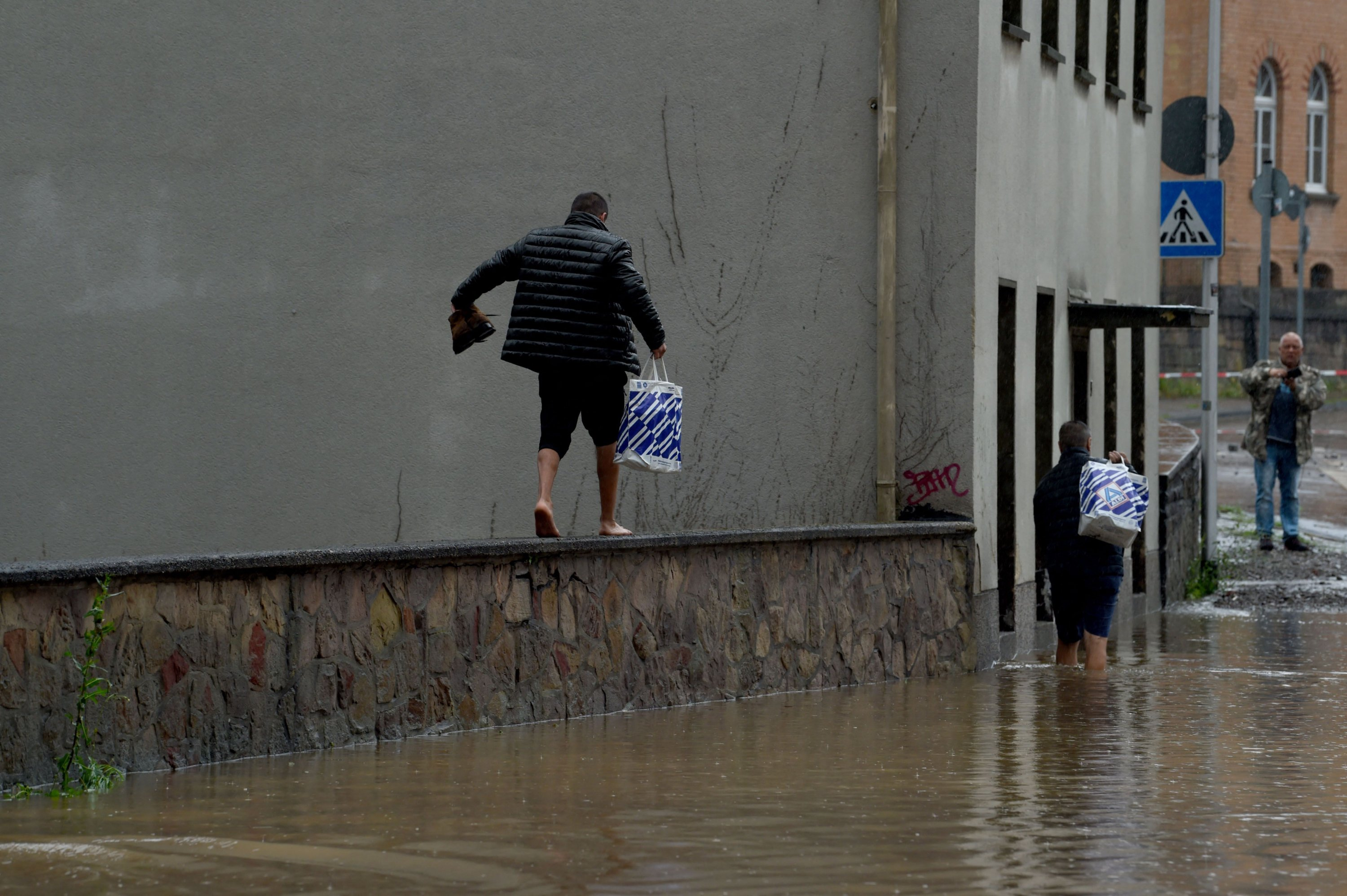 People carry bags through a flooded street in Hagen, western Germany, July 14, 2021, after heavy rain hit parts of the country, causing widespread flooding. (AFP Photo)
