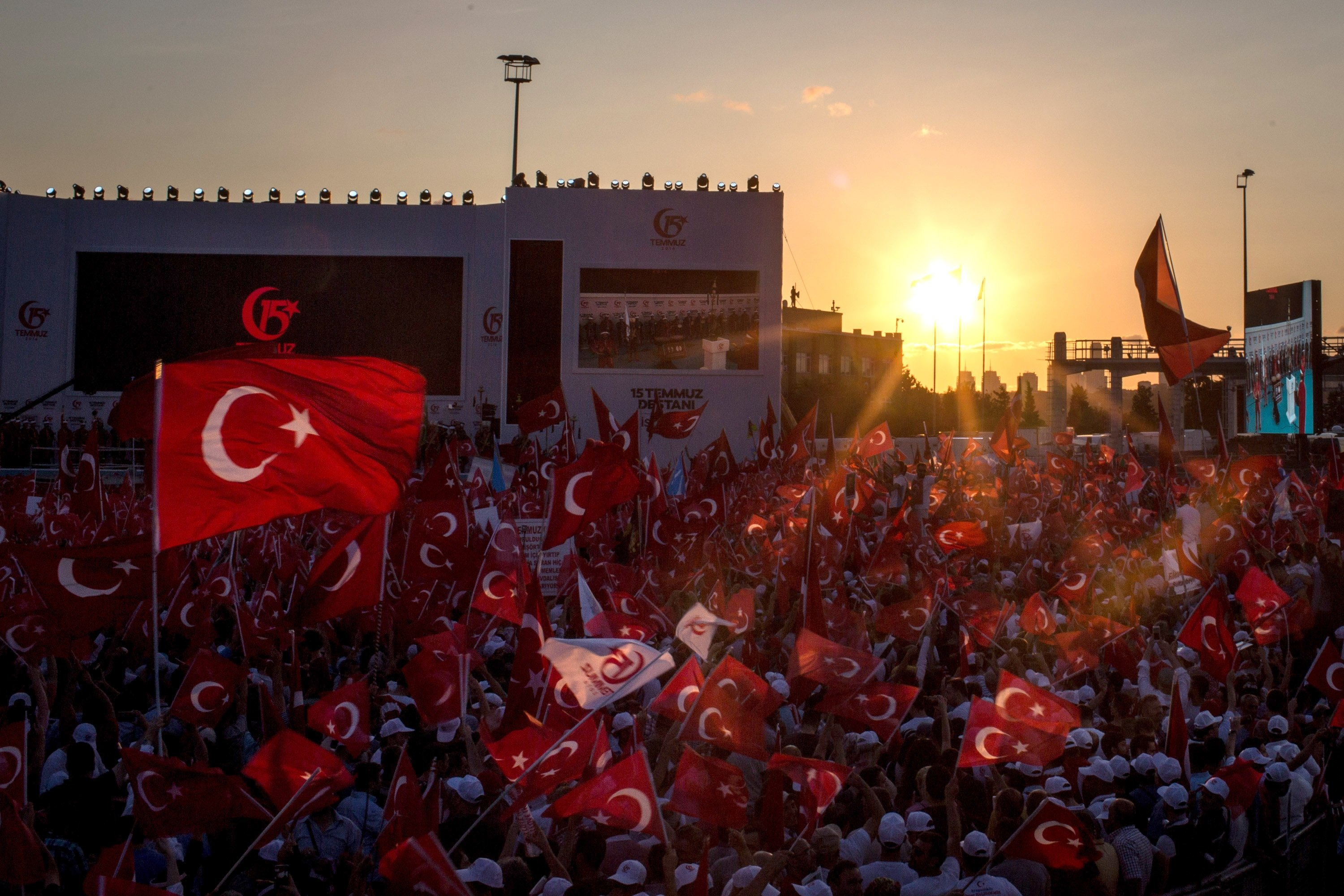People chant slogans and wave flags as they wait for official ceremonies to begin on the July 15 Martyrs Bridge on the first anniversary of the July 15, 2016 failed coup attempt, Istanbul, Turkey, July 15, 2017. (Photo by Getty Images)