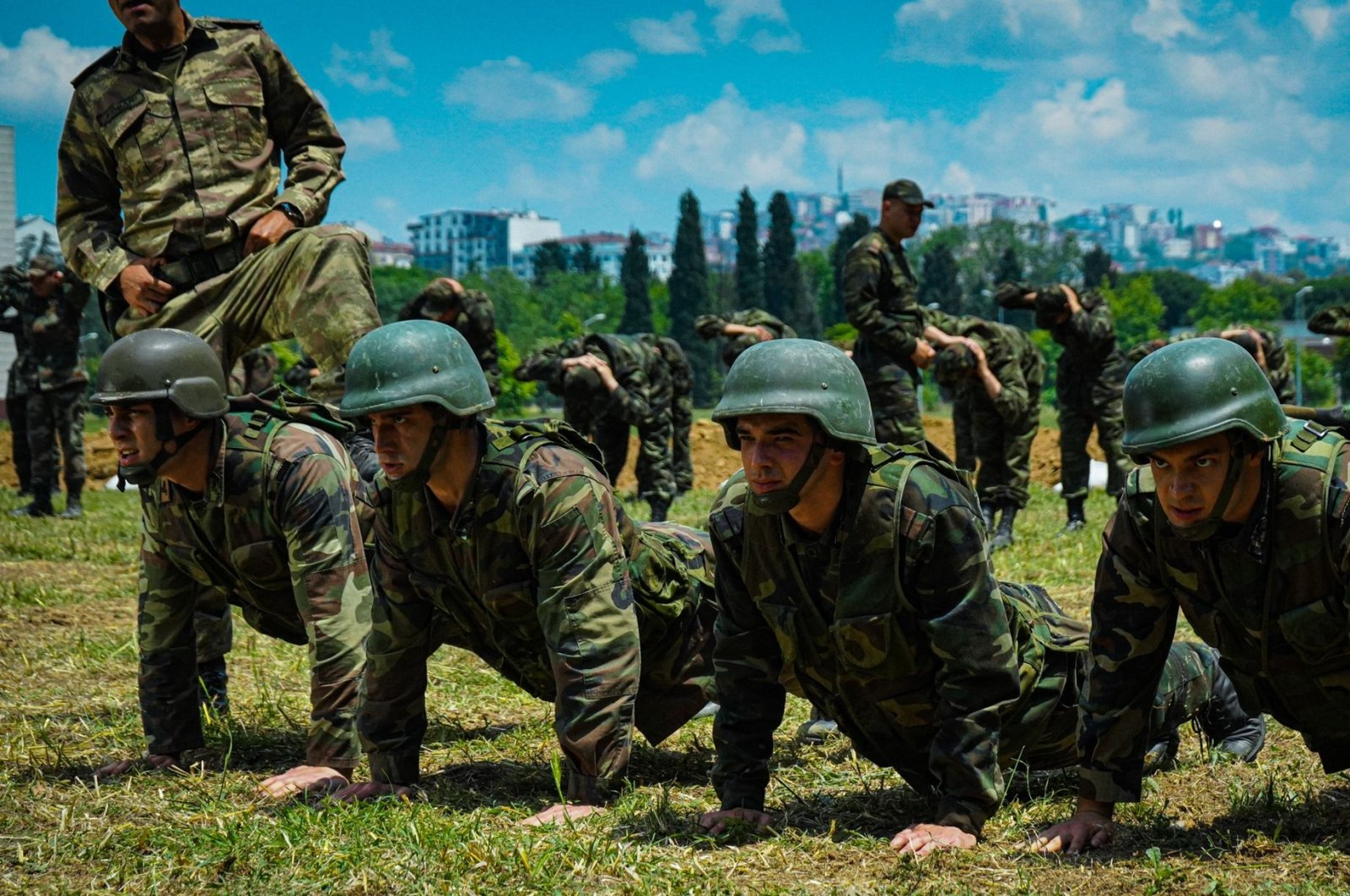 """Actors do push ups in a training course in a military complex, in a scene from the documentary series """"Mahrem."""" (AA)"""
