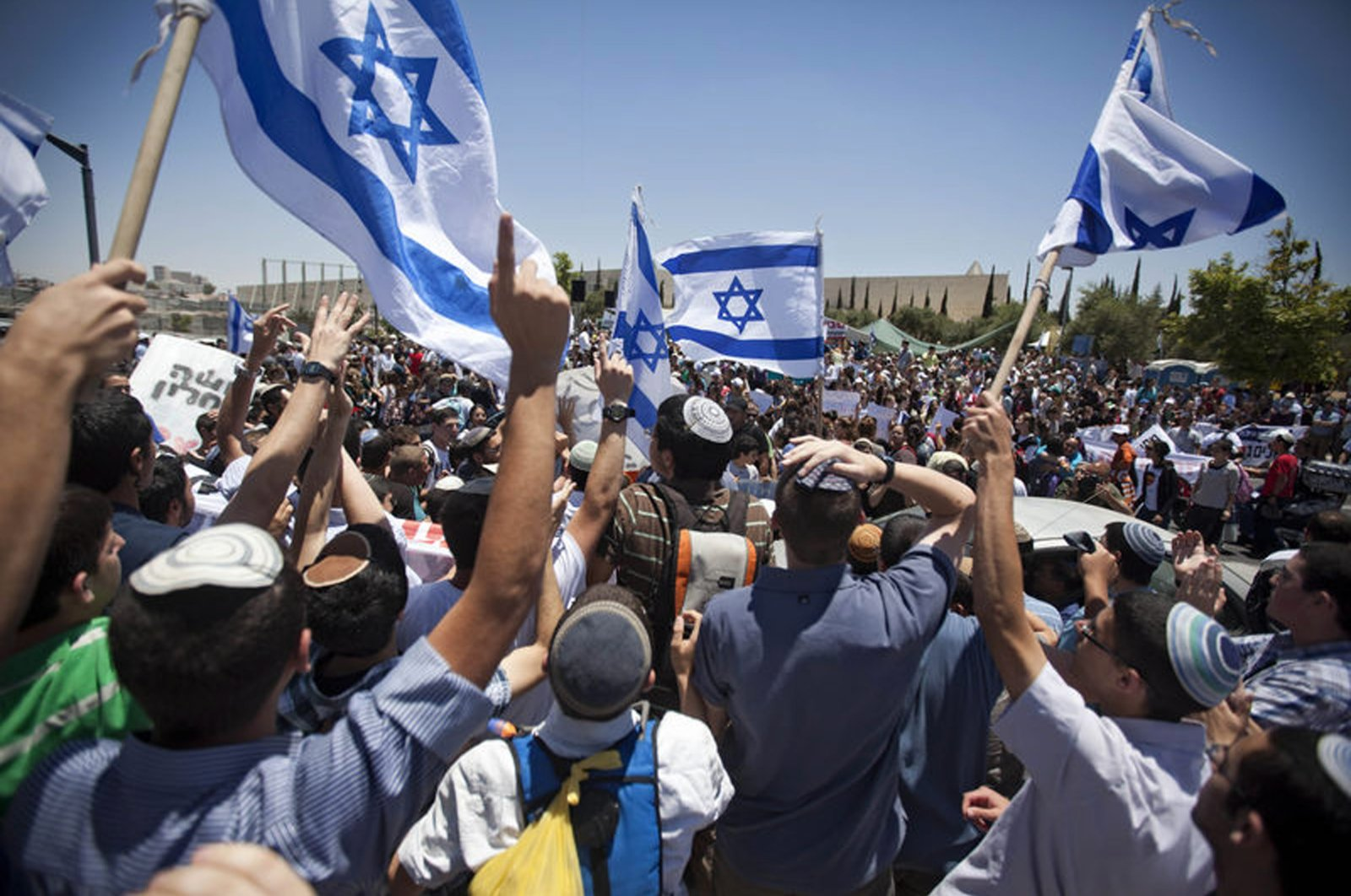 Israeli settlers wave flags during a protest outside the Supreme Court against the proposed decision to evacuate an occupied West Bank outpost in the Ulpana neighborhood, West Jerusalem, Israel, June 6, 2012. (AP Photo)