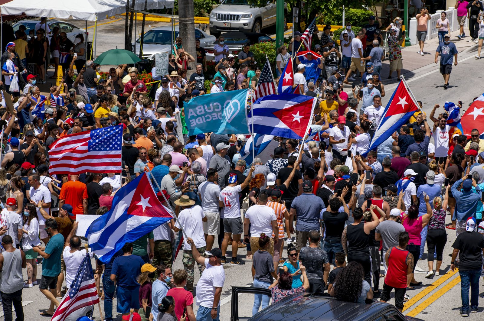 People march in the streets and wave Cuban flags during a protest in solidarity with thousands of Cubans who took to the streets in various locations in Cuba, in one of the largest protests to take place on the island, at Versailles Cuban restaurant off 8th Street in the Little Havana neighborhood of Miami, U.S., July 11, 2021. (AP Photo)