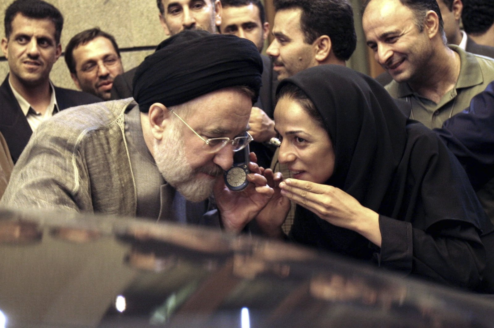 Outgoing reformist Iranian President Mohammad Khatami talks on the phone with the mother of female journalist Masih Alinejad, right, after meeting with journalists in Tehran, Iran, July 13, 2005. (AP Photo)