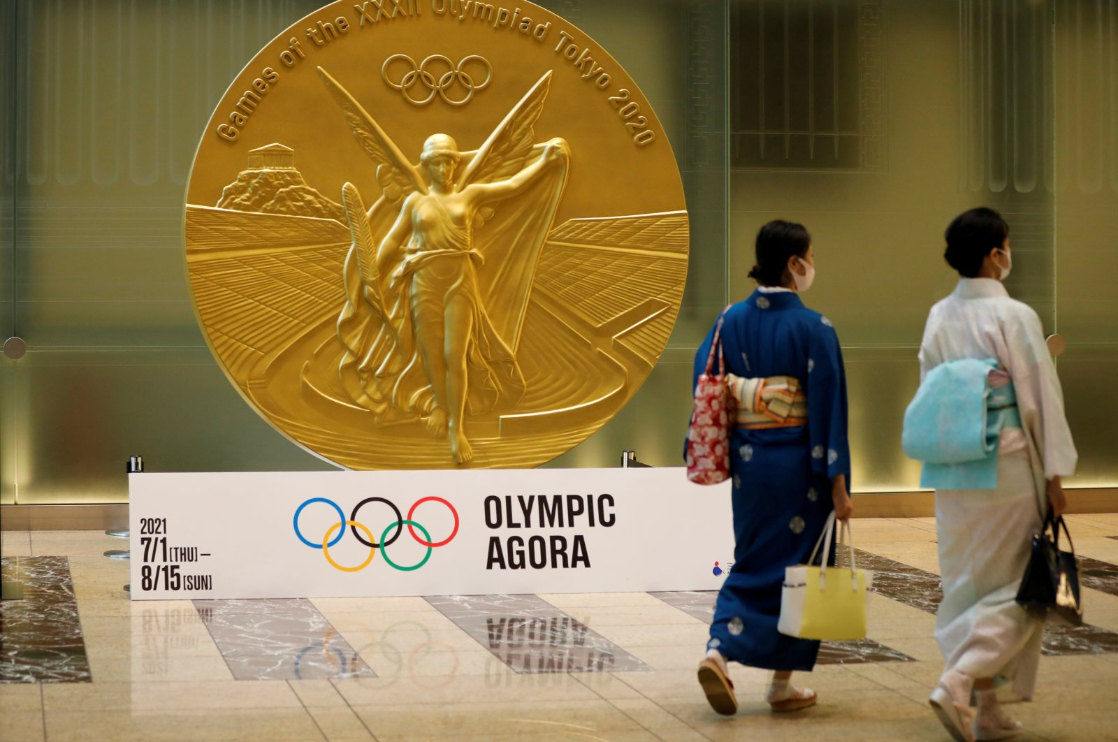 Women wearing protective masks against COVID-19, walk past a large-scale reproduction of the Tokyo 2020 Olympic Games medal at Nihonbashi Mitsui Tower in Tokyo, Japan, July 14, 2021.    (Reuters Photo)