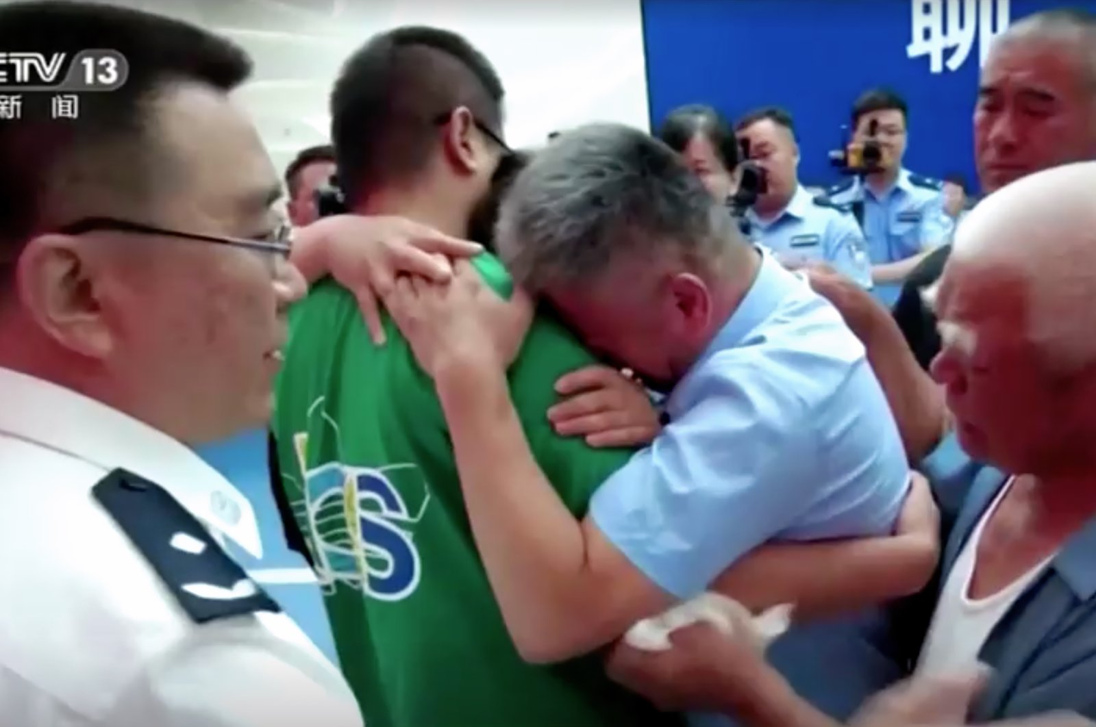 Guo Gangtang hugs his son, who was abducted when he was just two years and five months old. (Screenshot/CCTV via Reuters)