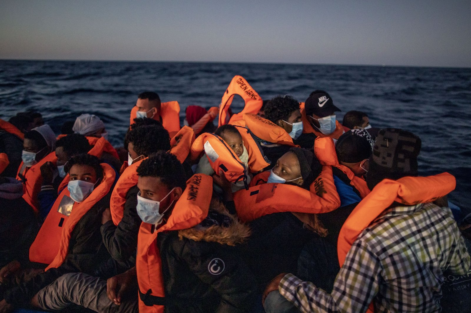 A woman holds a 3-month-old baby as migrants and refugees of different African nationalities wait for assistance on an overcrowded rubber boat from aid workers of the Spanish NGO Open Arms, 122 miles (around 196 kilometers) off the Libyan coast, Feb 12, 2021. (AP Photo)