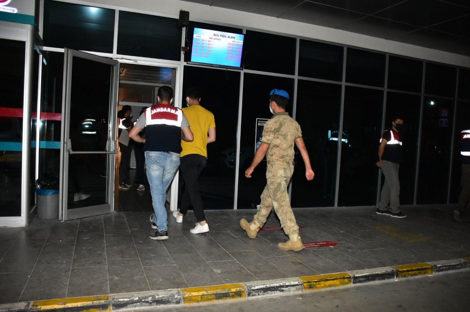 Gendarmerie officers escort a FETÖ suspect, in Izmir, western Turkey, July 12, 2021. (DHA PHOTO)