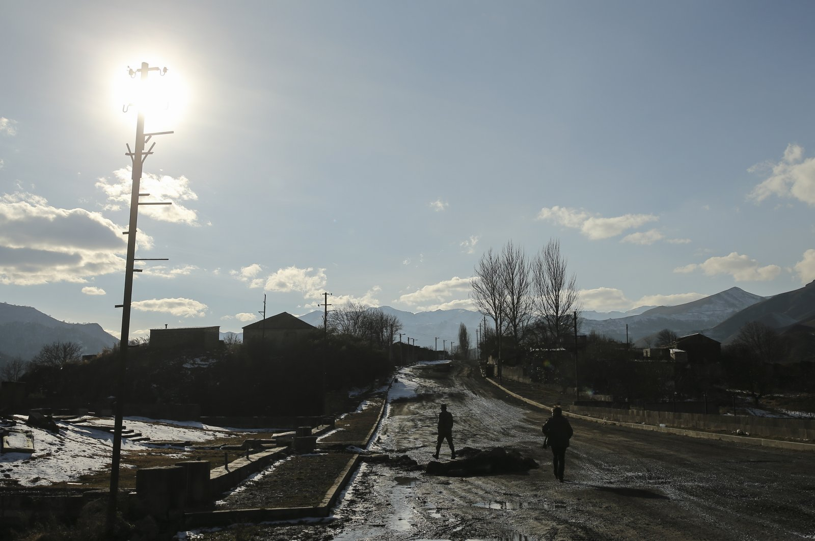 Azerbaijani soldiers walk on an empty road after the transfer of the Kalbajar region to Azerbaijan's control, as part of a peace deal that required Armenian forces to cede the Azerbaijani territories they held outside Nagorno-Karabakh, Kalbajar, Azerbaijan, Dec. 2, 2020. (AP File Photo/Emrah Gürel)