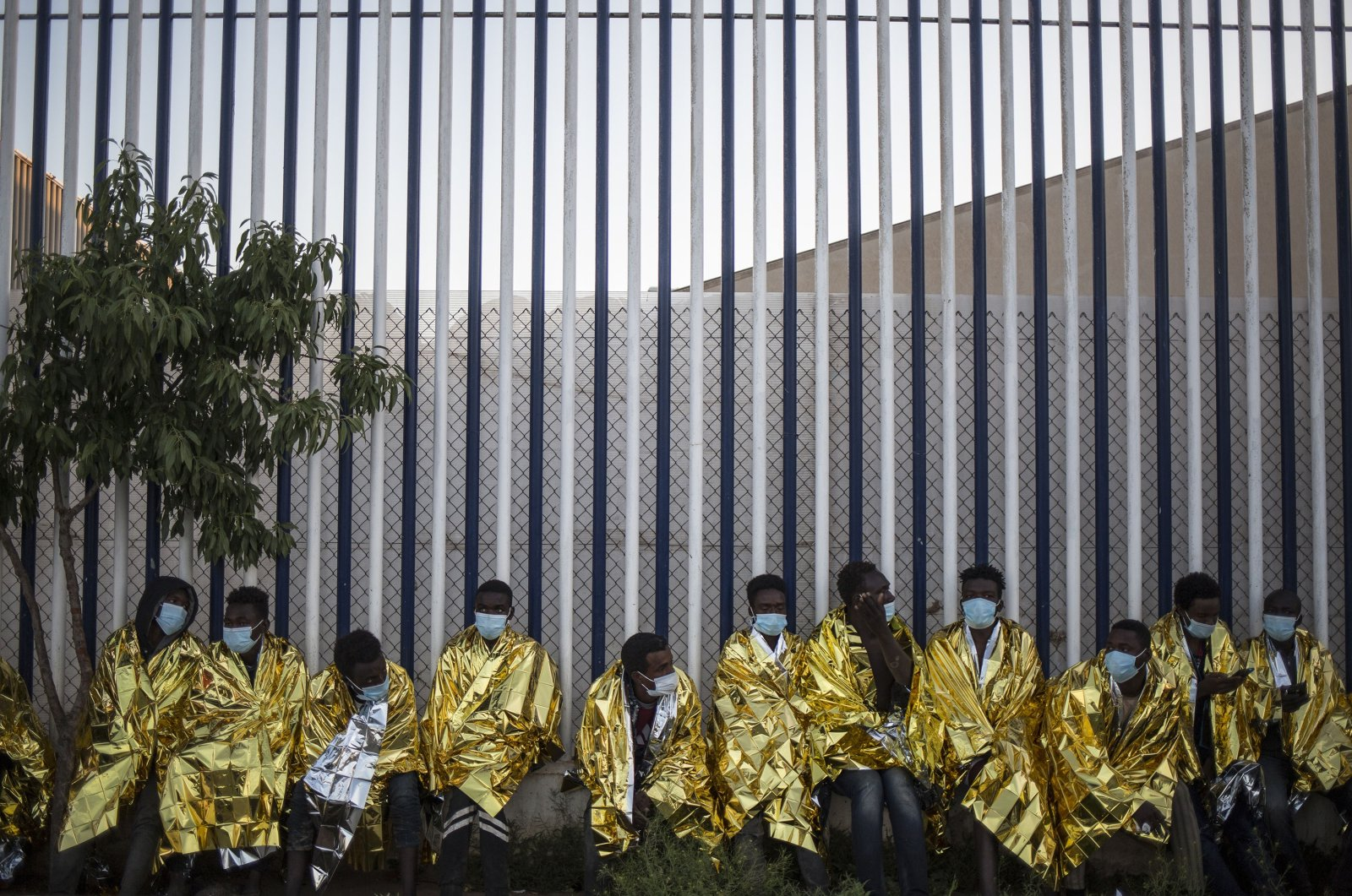 A group of migrants sits wrapped in thermal blankets at a holding center for migrants in the Spanish North African enclave of Melilla, Spain, May 18, 2021. (AP Photo)