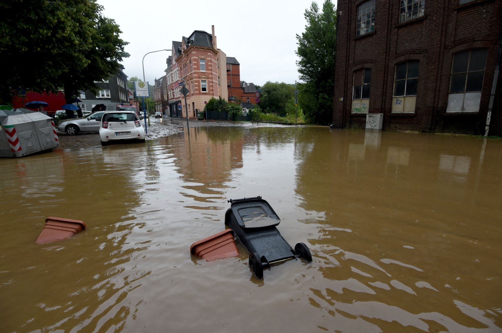 A dustbin and flowerpots float in a flooded street in Hagen, western Germany, July 14, 2021, after heavy rain hit parts of the country, causing widespread flooding. (AFP Photo_