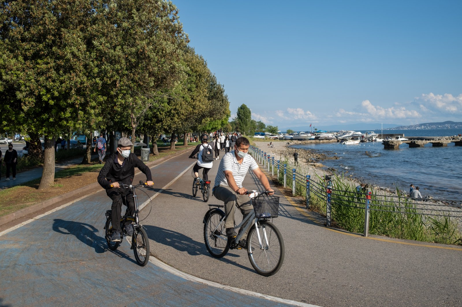 People wearing protective masks against COVID-19 ride bicycles in Istanbul, Turkey, June 1, 2021. (GETTY IMAGES)
