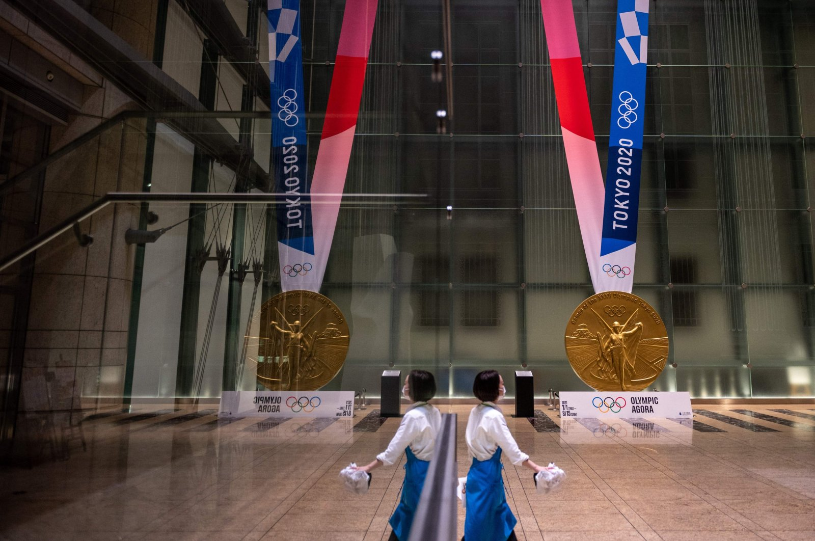 A woman walks near a large-scale reproduction of the Tokyo 2020 Olympic Games gold medal as part of the Olympic Agora event at Mitsui Tower, Tokyo, Japan, July 14, 2021. (AFP Photo)