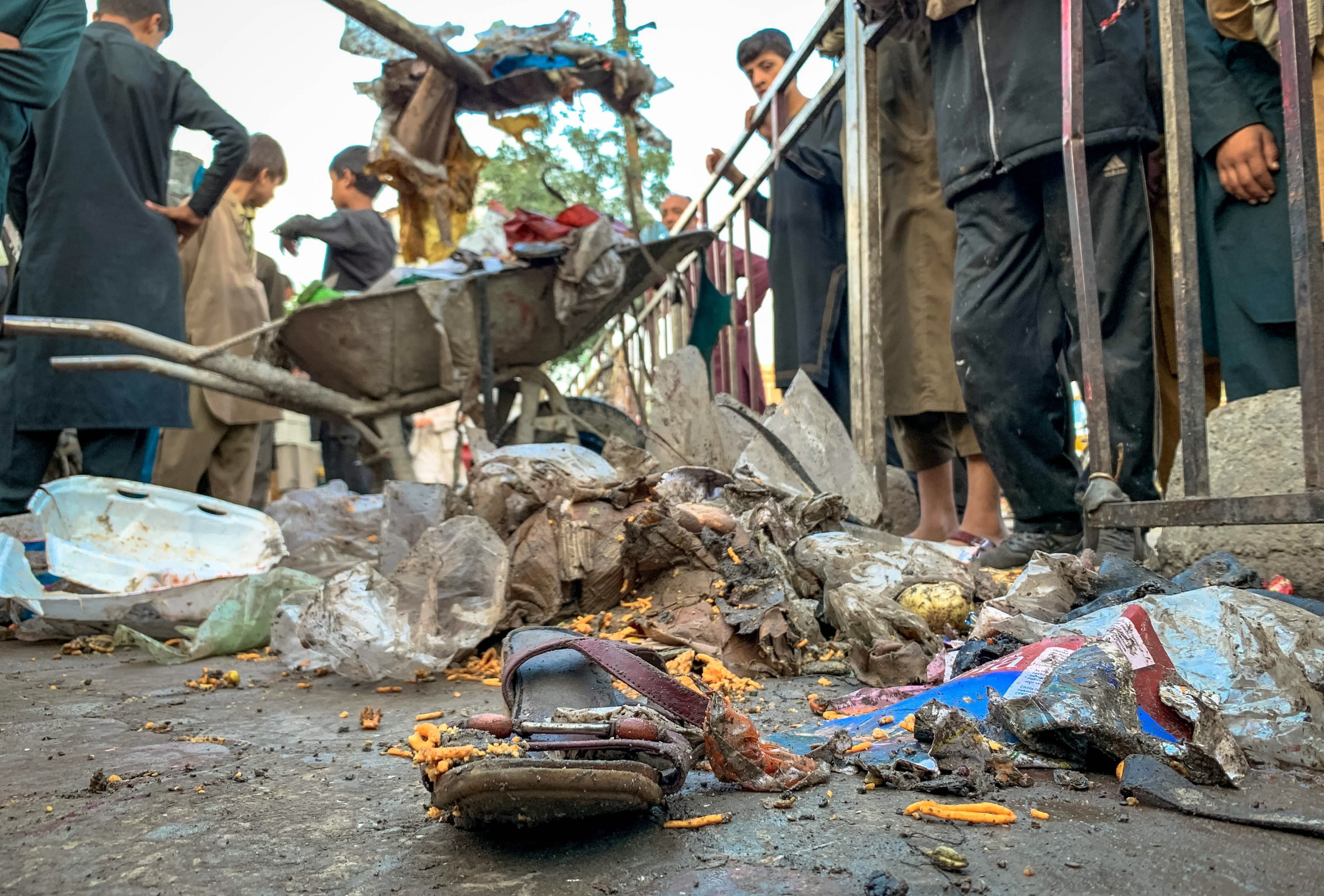 Afghan people watch personal belongings of victims as municipality workers clean the scene after a bomb explosion in Kabul, Afghanistan, July 13, 2021. (EPA Photo)