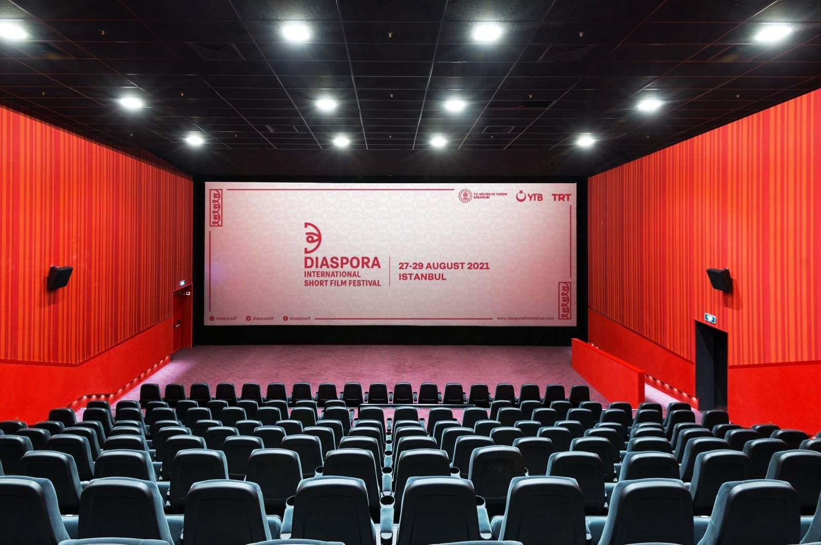 A panoramic view of an empty movie theater with a screen. (Shutterstock Photo)