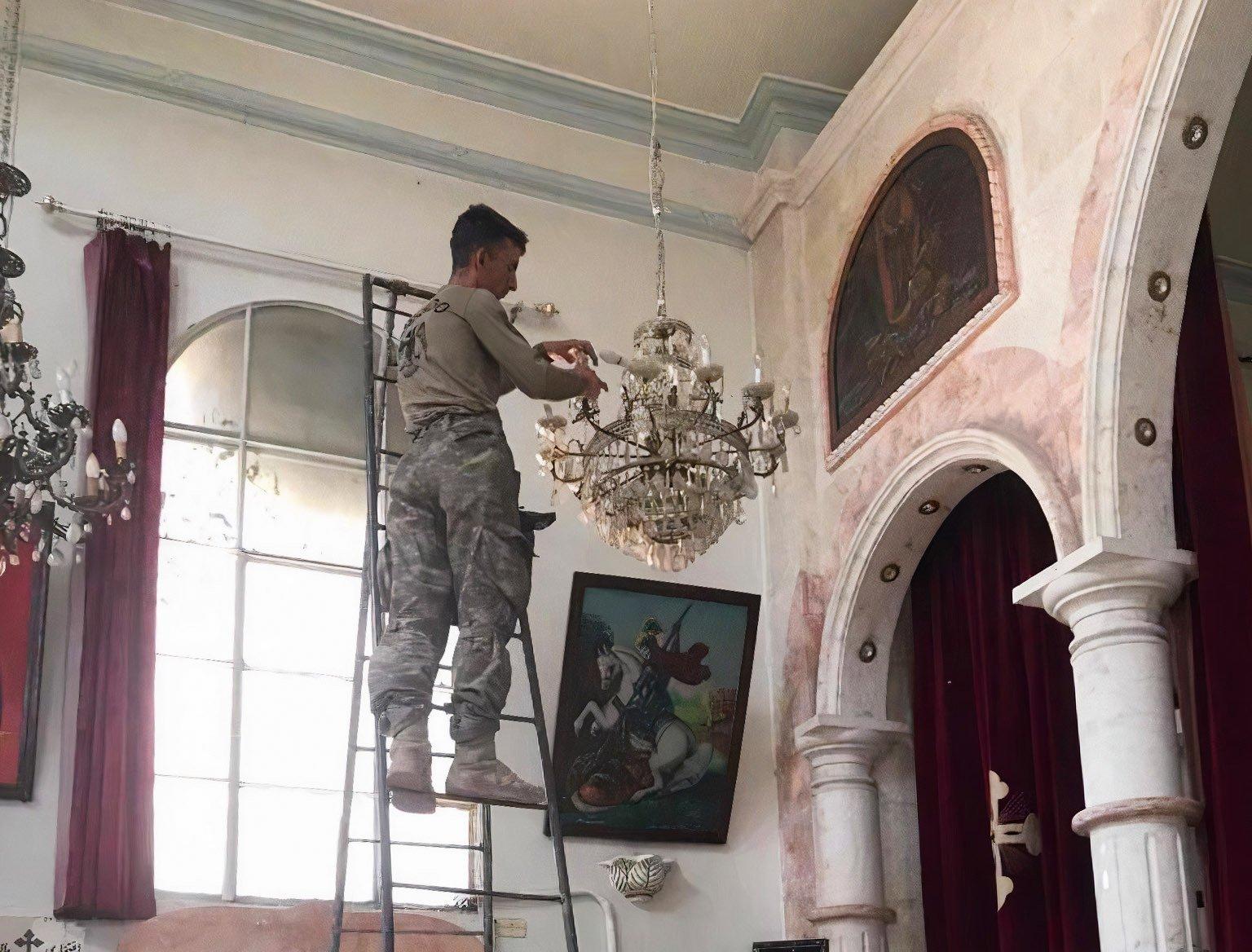 A Turkish soldier installs lightbulbs on a chandelier inside the Syriac Orthodox Church in Syria's Ras al-Ain, July 14, 2021. (Defense Ministry Handout)