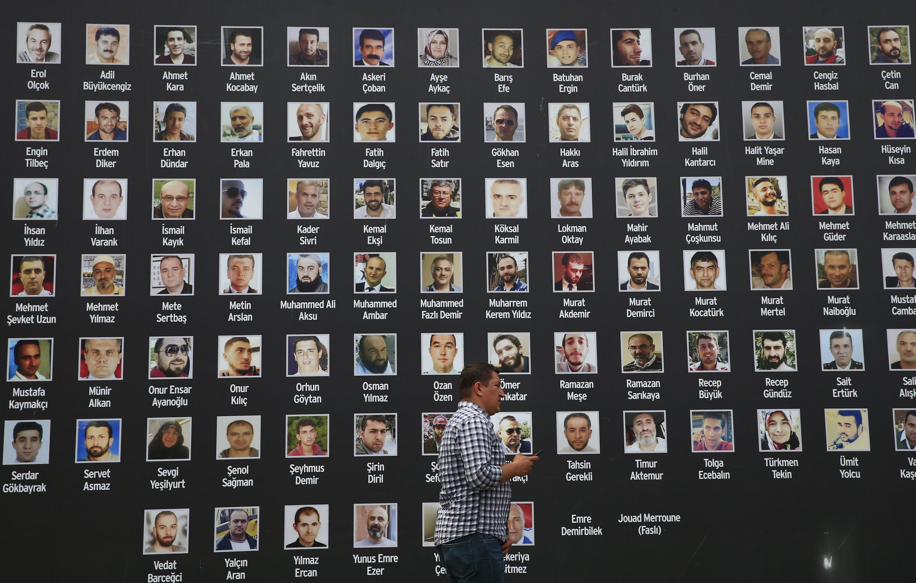 A man walk past a poster of photographs of victims of the July 15, 2016 coup attempt, in Istanbul, Turkey, July 14, 2017. (AP Photo)