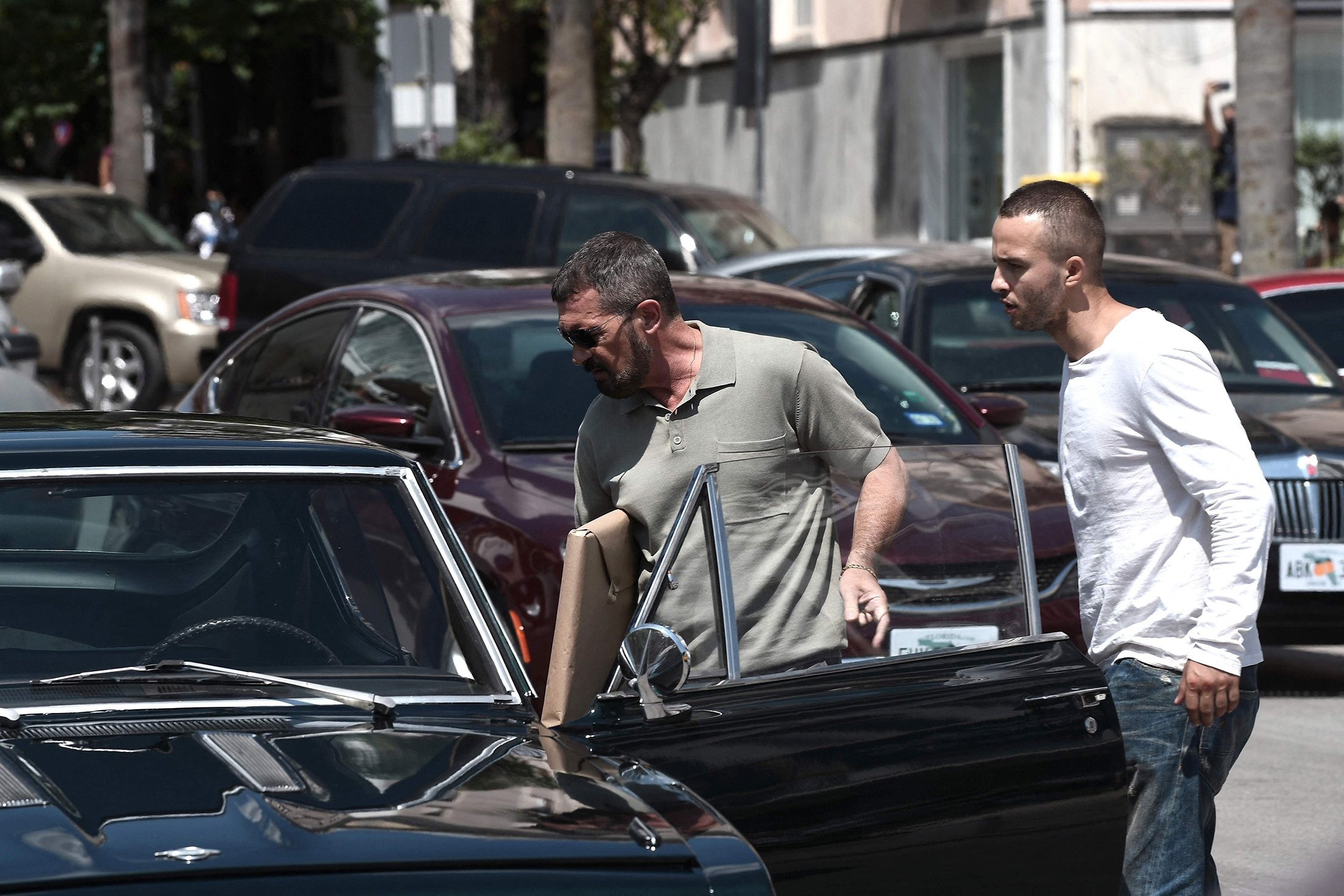 Spanish actor, director and producer Antonio Banderas (L) enters a car, flanked by a crew member during the filming of the action thriller, 'The Enforcer,' in the streets of Thessaloniki, Greece, July 3, 2021. (AFP Photo)