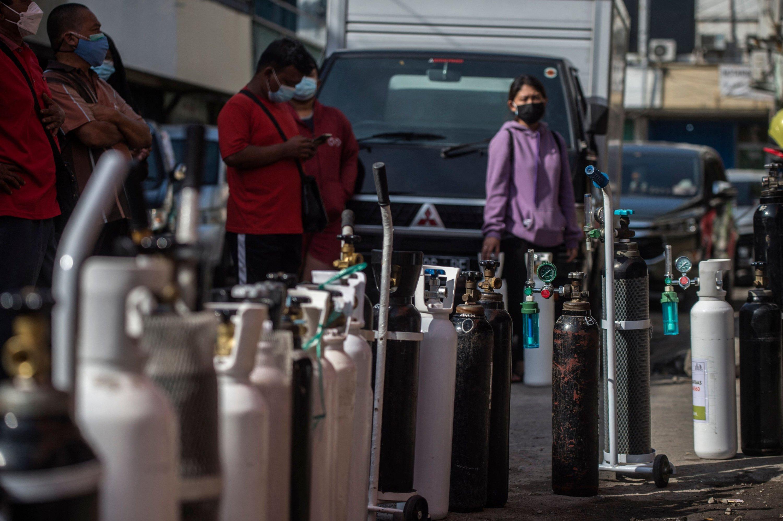 Pada 15 Juli 2021, warga mengantre untuk mengisi tangki oksigen di SPBU di Surabaya, kota terbesar kedua di Indonesia, menyusul perintah pemerintah untuk mengirim pasokan oksigen negara ke rumah sakit yang penuh sesak dengan pasien COVID-19.  (foto AFP)