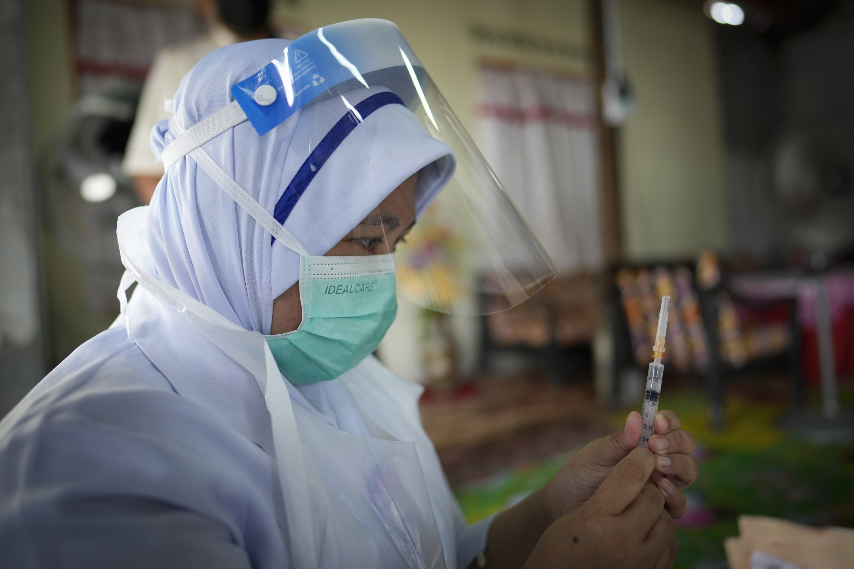 Pada 13 Juli 2021, seorang perawat bersiap untuk memberikan vaksin Pfizer-Biotech Govit-19 kepada seorang wanita lanjut usia di rumahnya di pedesaan Sabab Bernam, Selangor tengah, Malaysia.  (foto AP)