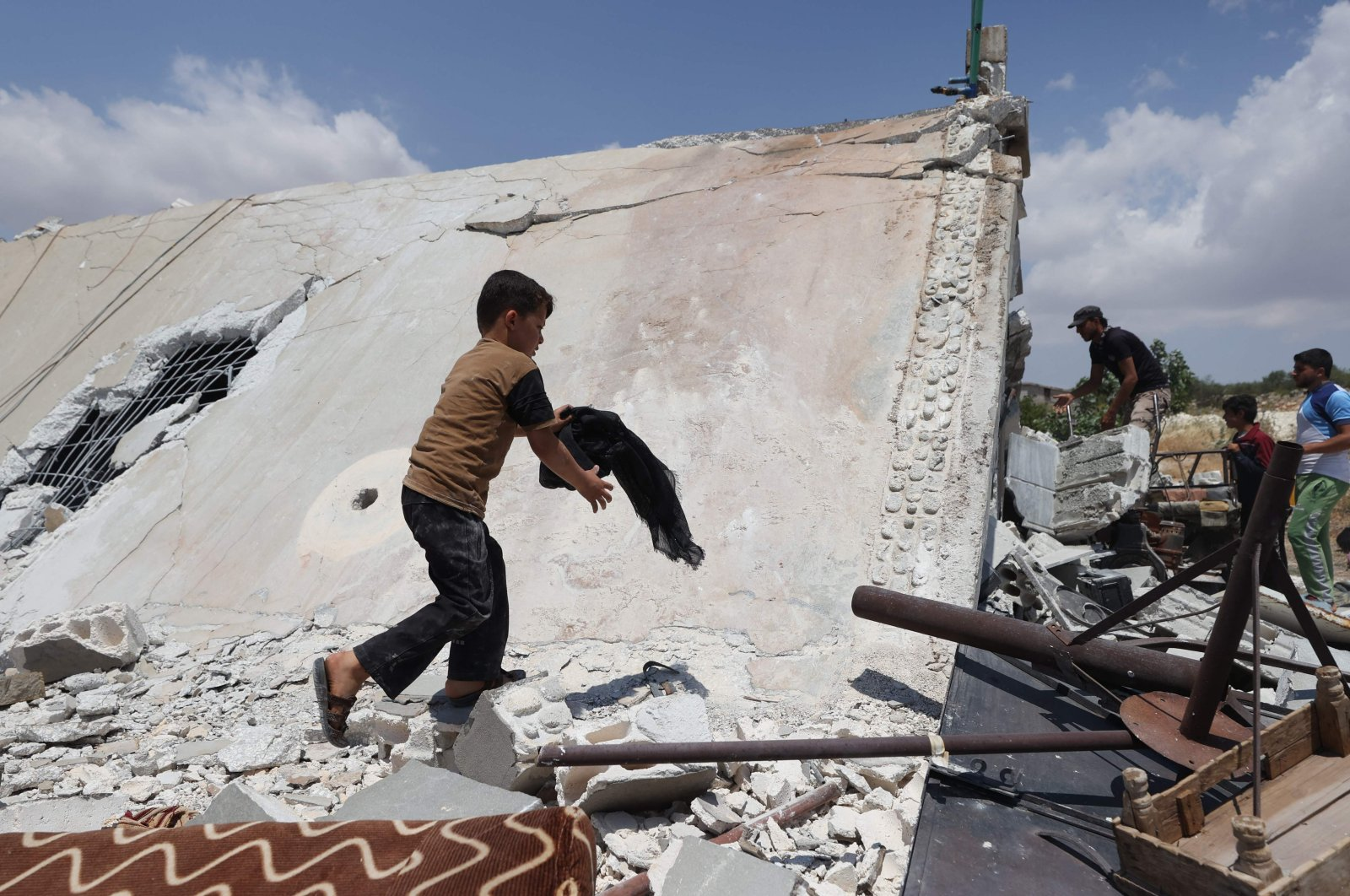 A young boy salvages belongings from a house destroyed by a Russian missile attack in the Jabal al-Zawiya region in the south of Syria's opposition-held Idlib province, on July 4, 2021. (AFP Photo)