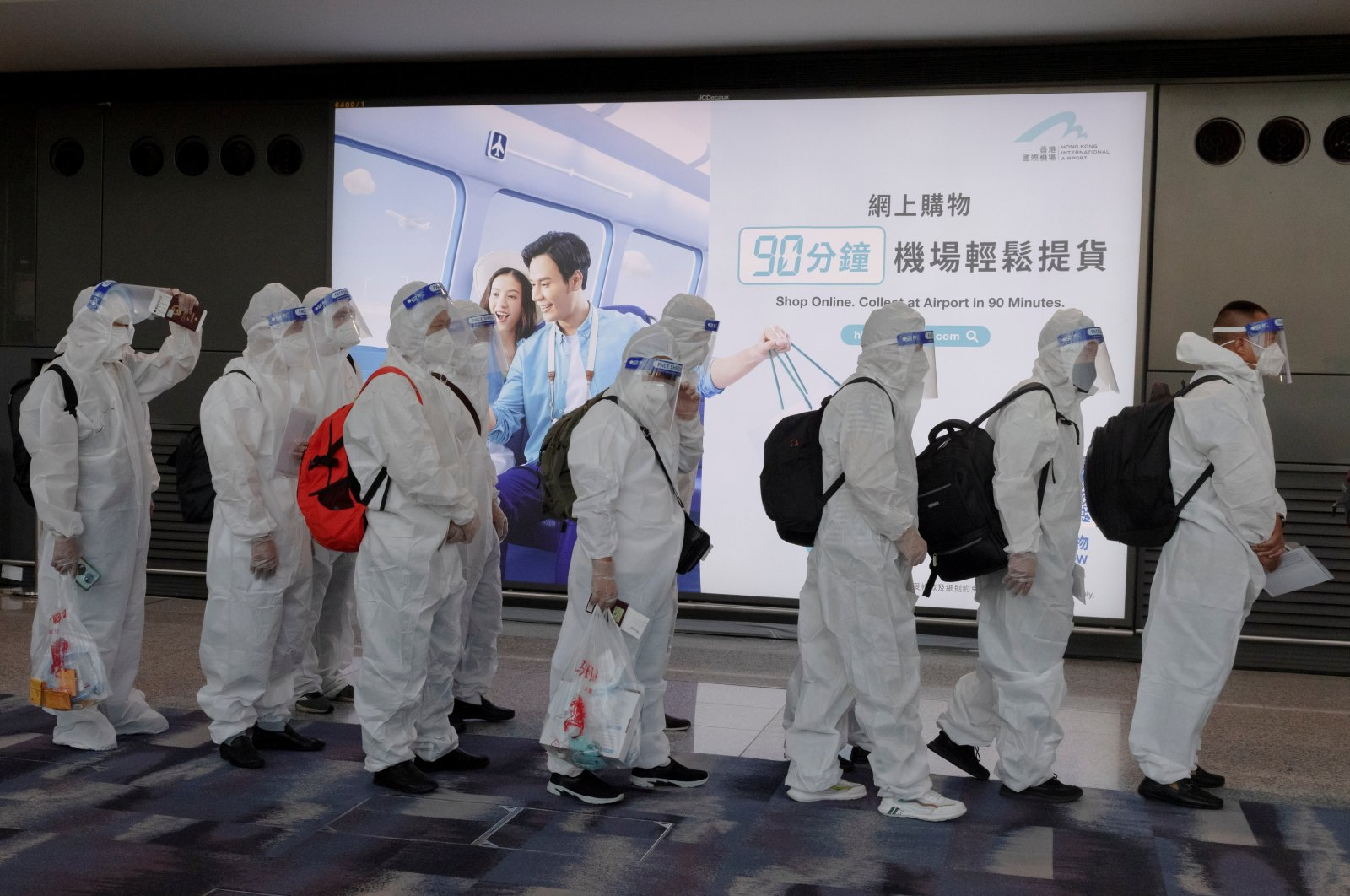 Passengers wearing protective suits (PPE) to protect themselves against COVID-19 line up to board their plane for an international flight at Hong Kong airport, China, July 9, 2021. (Reuters Photo)
