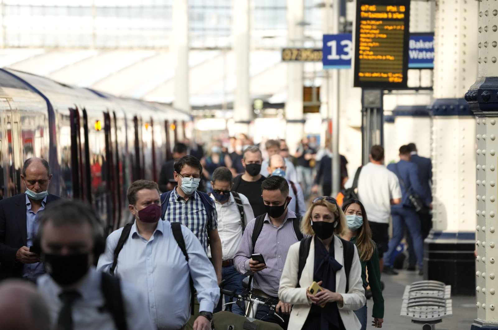 People wear face masks to curb the spread of the coronavirus as they disembark from a train during the morning rush hour at Waterloo train station in London, UK, July 14, 2021. (AP Photo)