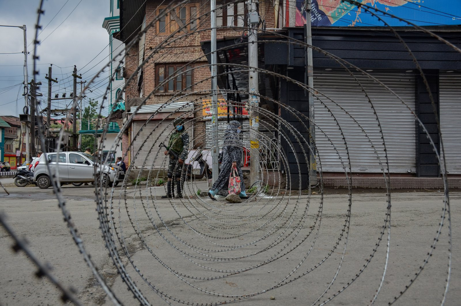 A woman walks past a concertina barricade erected by the Indian forces during restrictions imposed on the eve of Martyrs Day in old city of Srinagar, Indian-controlled Kashmir, July 13, 2021. (Photo by Getty Images)
