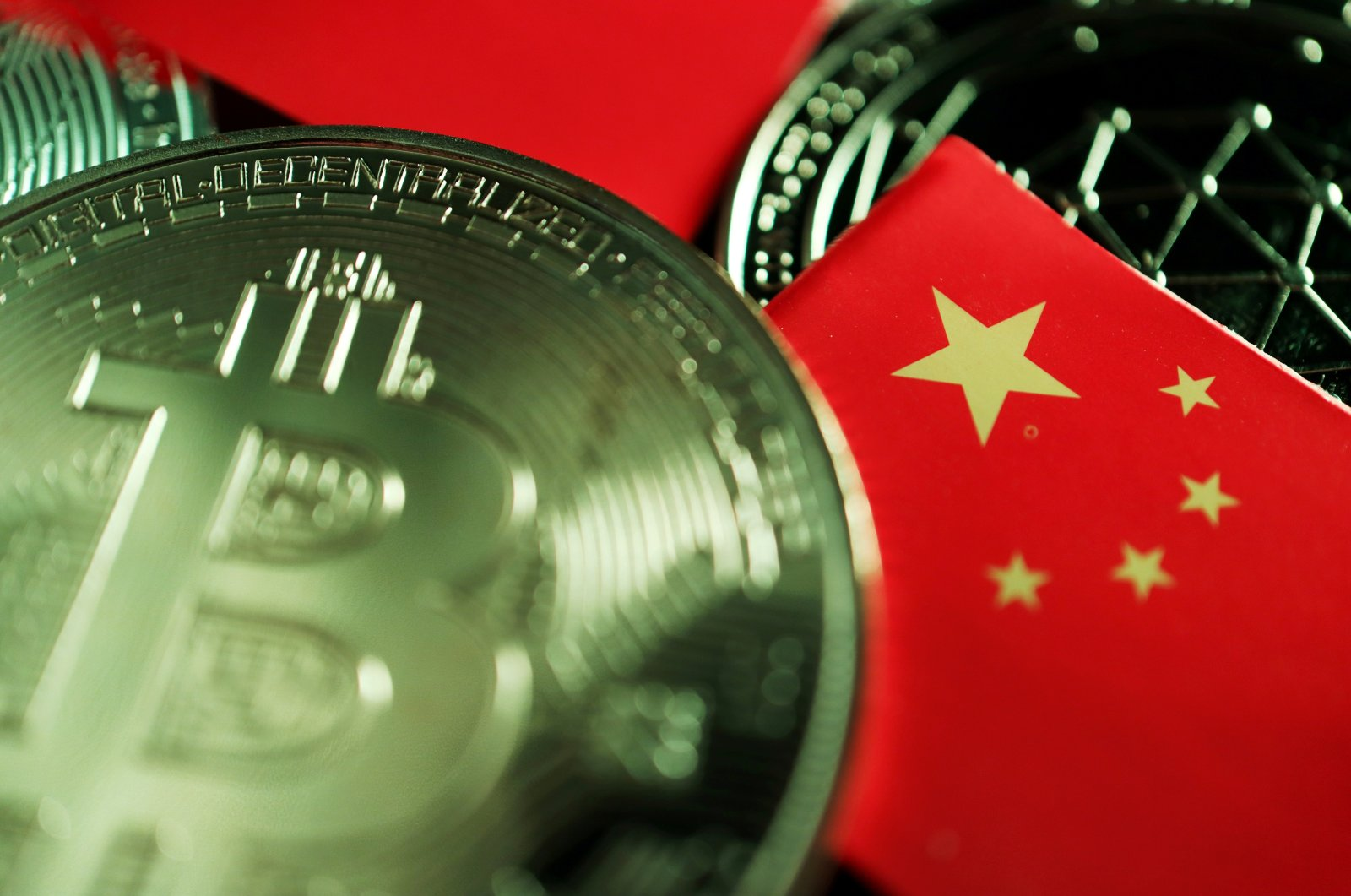 A Chinese flag is seen among representations of Bitcoin and other cryptocurrencies in this illustration picture taken June 2, 2021. (Reuters Photo)