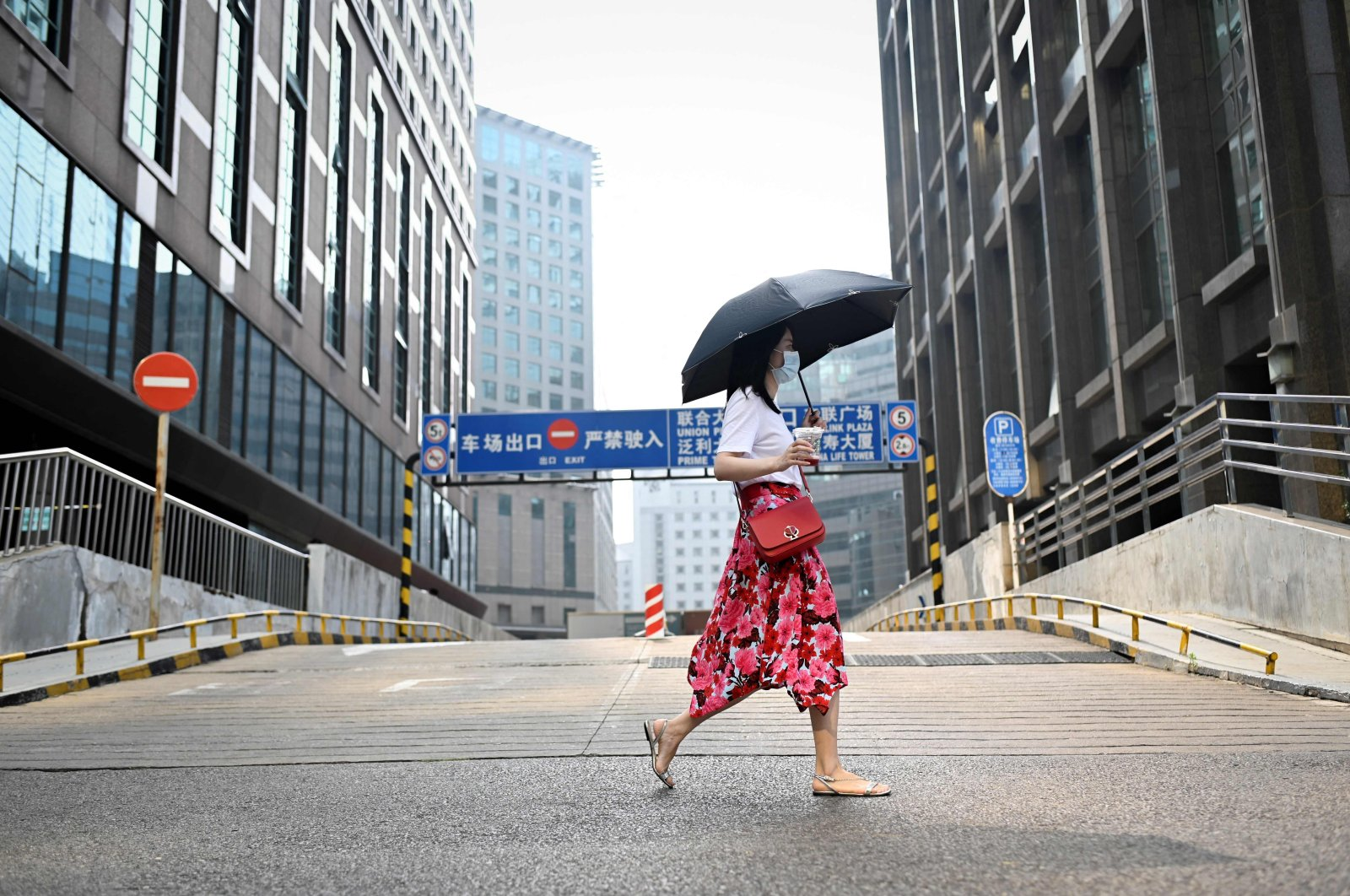 A woman walks past an office building in Beijing, China, July 15, 2021. (AFP Photo)