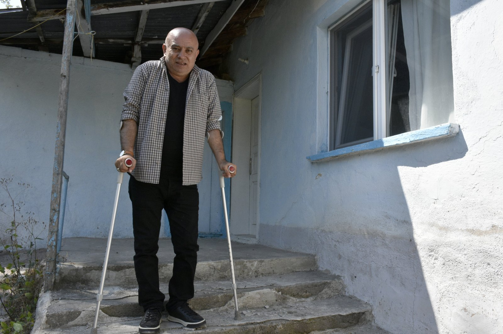 Yaşar Parlak stands outside his house, leaning on his crutches, in Gümüşhane, northern Turkey, July 14, 2021. Parlak was left injured by putschists in Istanbul in 2016. (AA PHOTO)