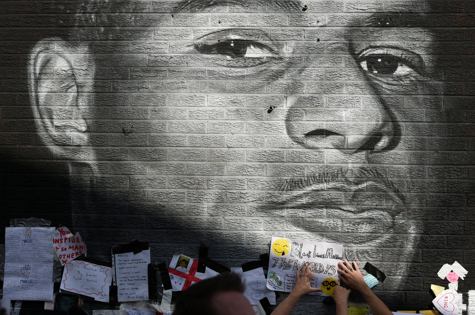 FILE PHOTO: Stand Up to Racism Demonstration at the Marcus Rashford mural after it was defaced following the Euro 2020 Final between Italy and England - Withington, Manchester, Britain - July 13, 2021 People attach a message of support on the Marcus Rashford mural after it was defaced following the Euro 2020 Final between Italy and England REUTERS/Peter Powell/File Photo