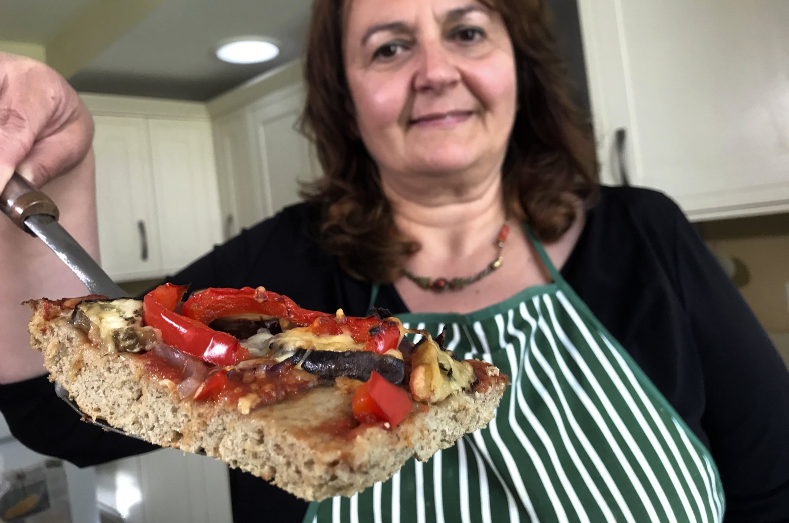 Tiziana di Costanzo, co-founder of Horizon Insects, holds up a slice of pizza made with cricket powder, in her London kitchen, London, U.K., June 2, 2021. (AP Photo)