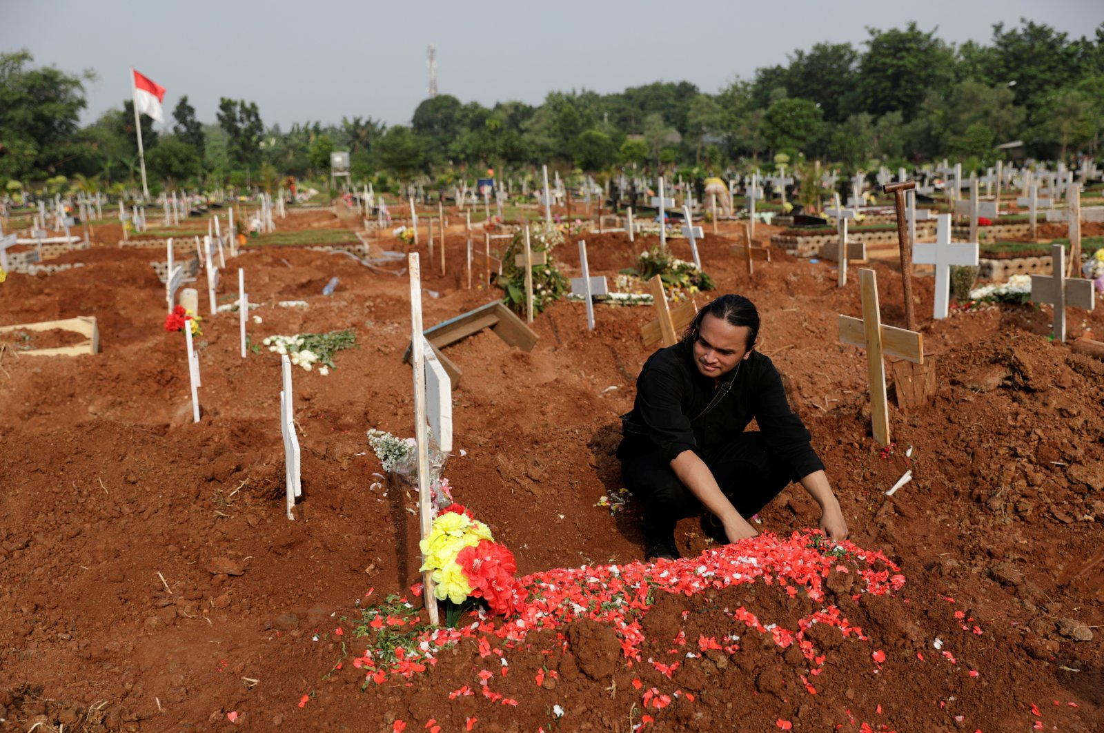 Risalvy H. A., 23, mourns at the grave of his 65-year-old father who passed away due to COVID-19, during the funeral at a burial area provided by the government for COVID-19 victims as the cases surge, in Bekasi, on the outskirts of Jakarta, Indonesia, July 15, 2021. (Reuters Photo)