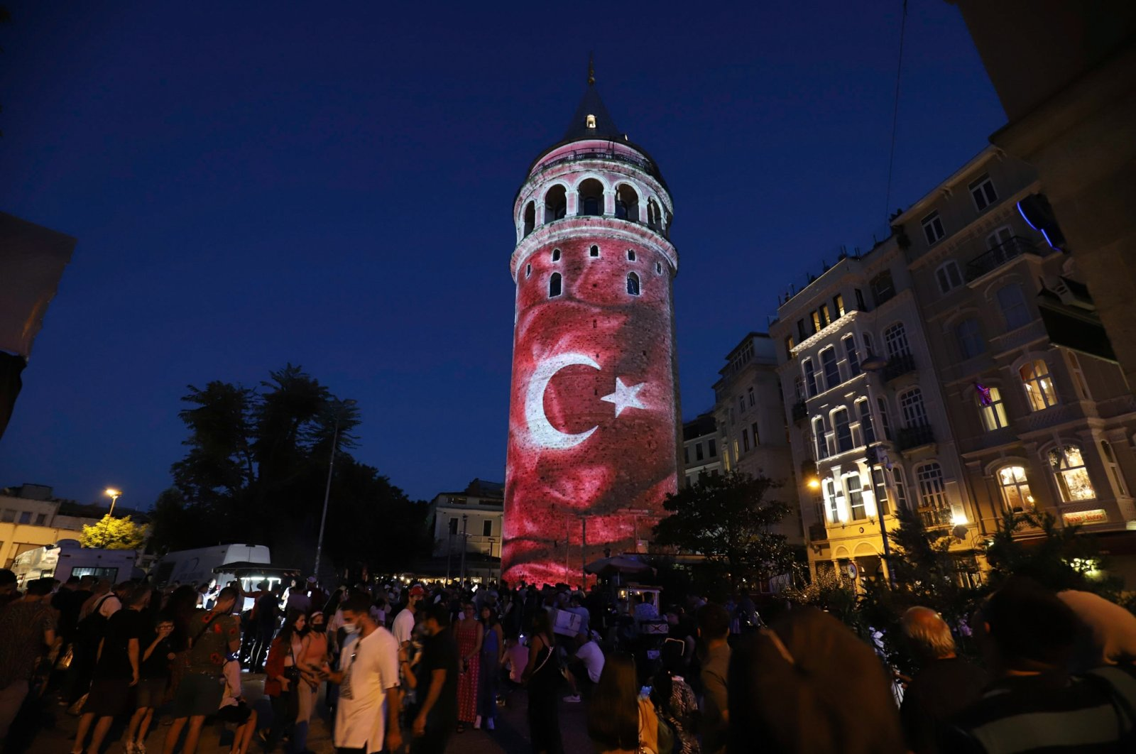People walk past the Galata Tower with the national Turkish flag reflected to mark the July 15 Democracy and National Unity Day, Istanbul, Turkey, July 15, 2021. (AA Photo)