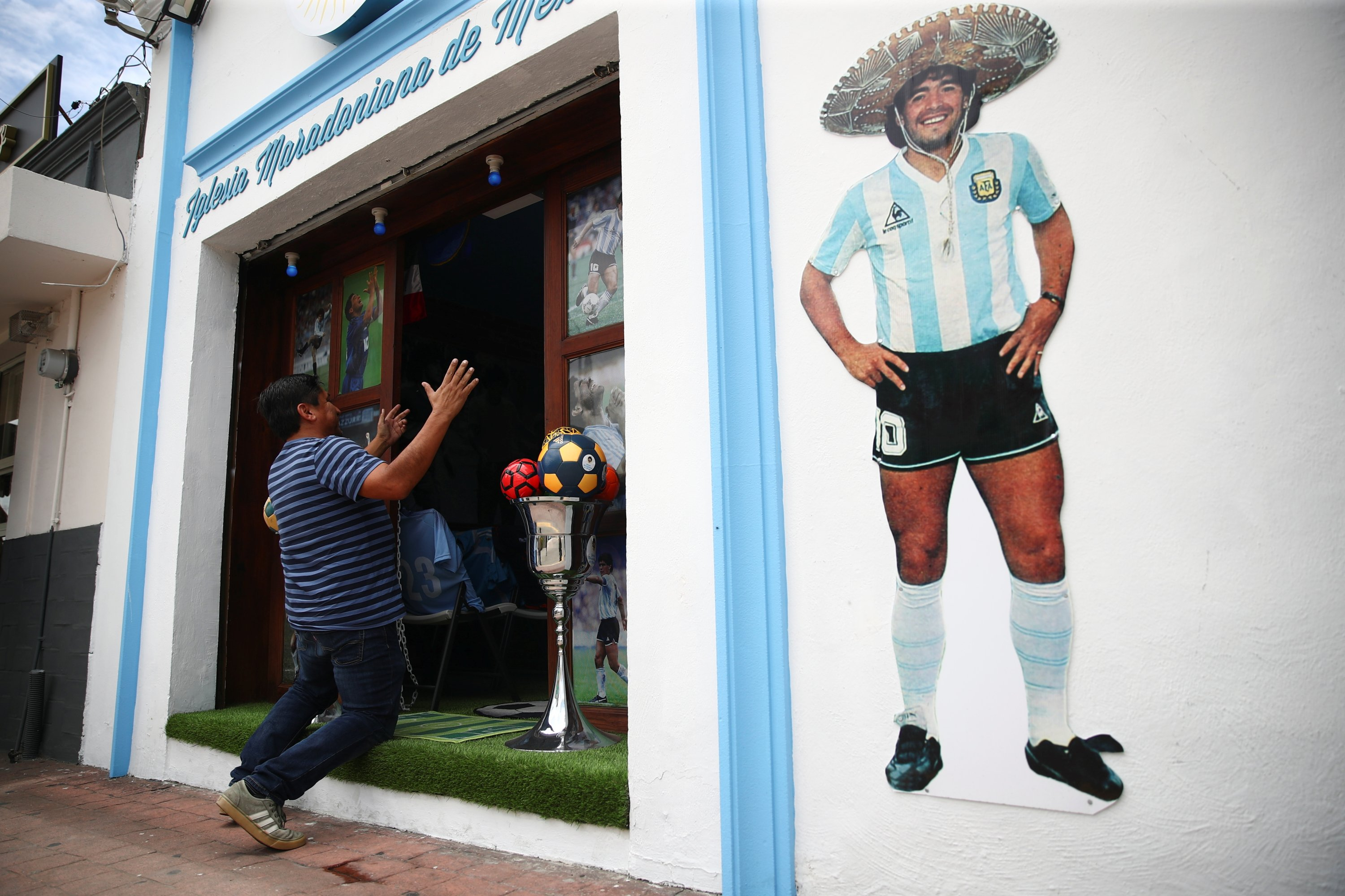 A fan kneels at the entrance to Mexico's first church in memory of football legend Diego Maradona in San Andres Cholula, in Puebla state, Mexico, July 14, 2021. (Reuters Photo)