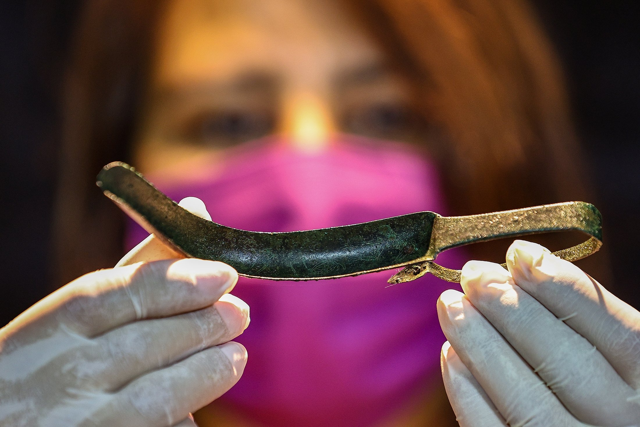 """An official presents the ancient artifact known as a """"strigil,"""" a historical tool used for cleansing gladiators, on exhibition at Izmir Archaeological Museum in Izmir, Turkey, July 15, 2021. (AA Photo)"""