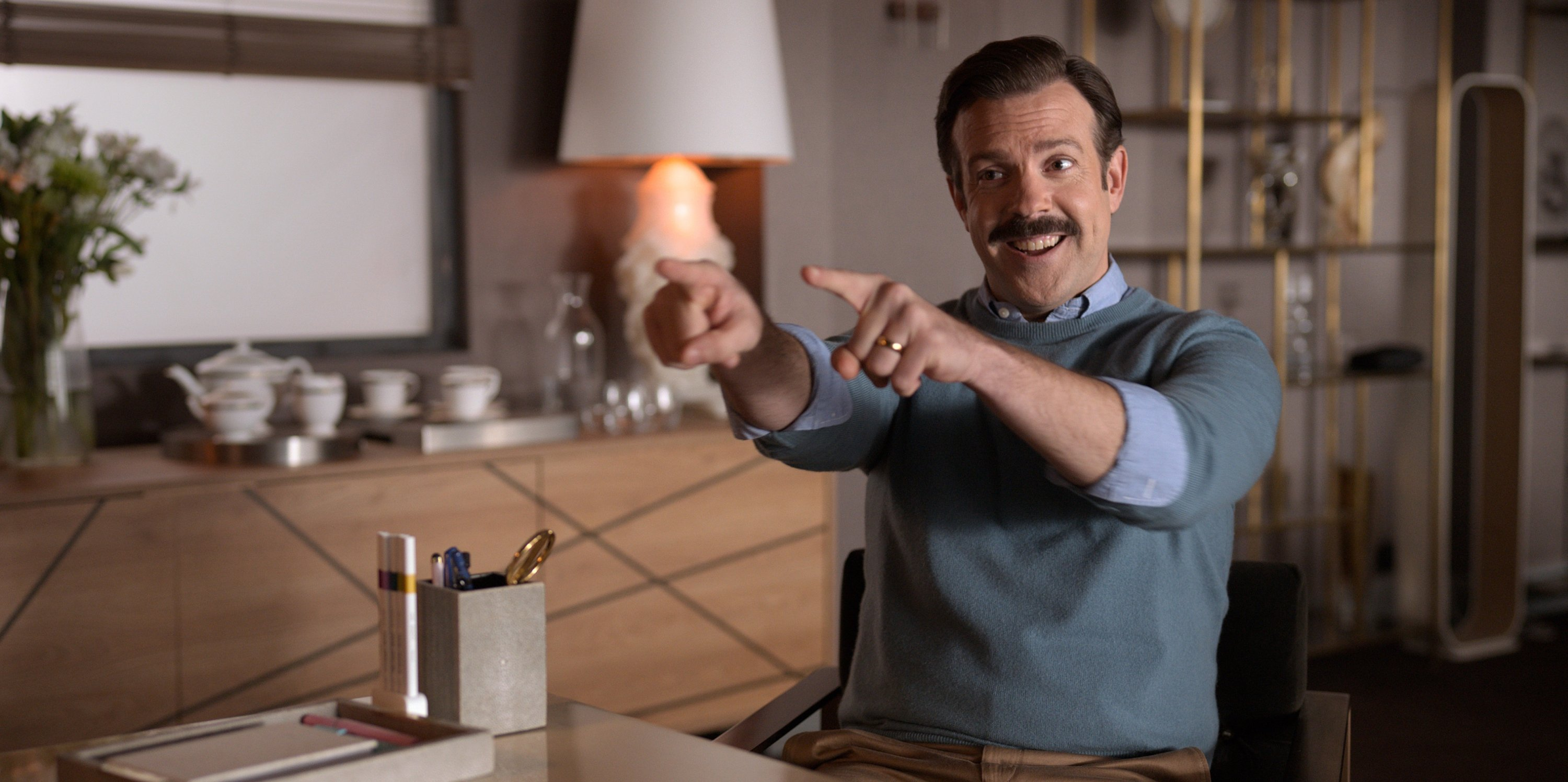 Jason Sudeikis, as Ted Lasso, points his fingers as he smiles, in a scene from the series 'Ted Lasso.' (Apple TV+ via AP)