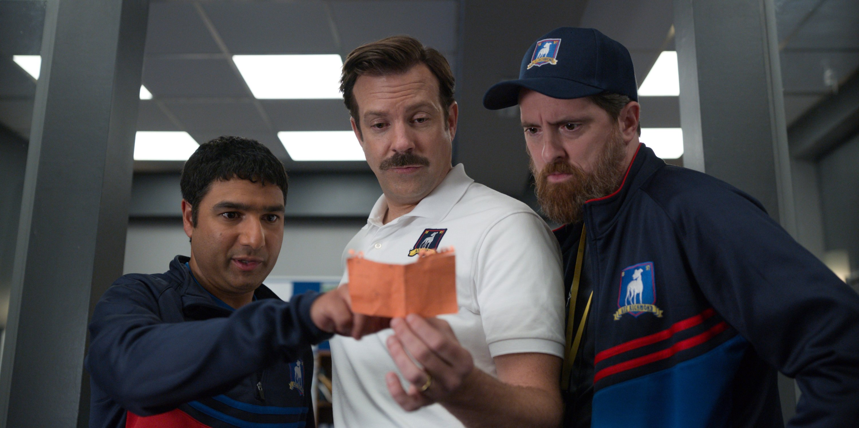 Jason Sudeikis (C), as Ted Lasso, Nick Mohammed (L) and Brendan Hunt inspect a paper, in a scene from the series 'Ted Lasso.' (Apple TV+ via AP)