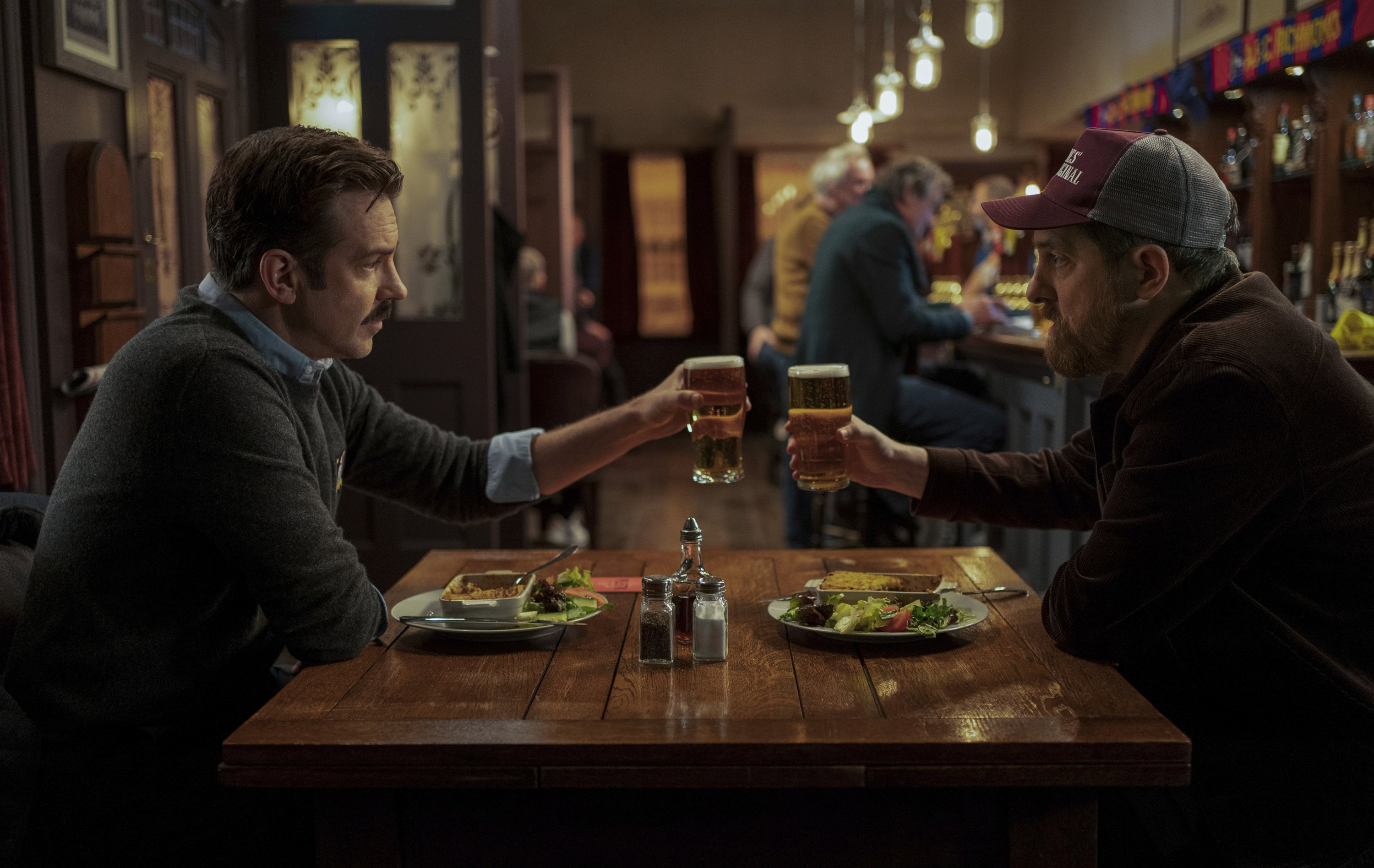 Jason Sudeikis (L), as Ted Lasso, and Brendan Hunt toast their glasses, in a scene from the series 'Ted Lasso.' (Apple TV+ via AP)
